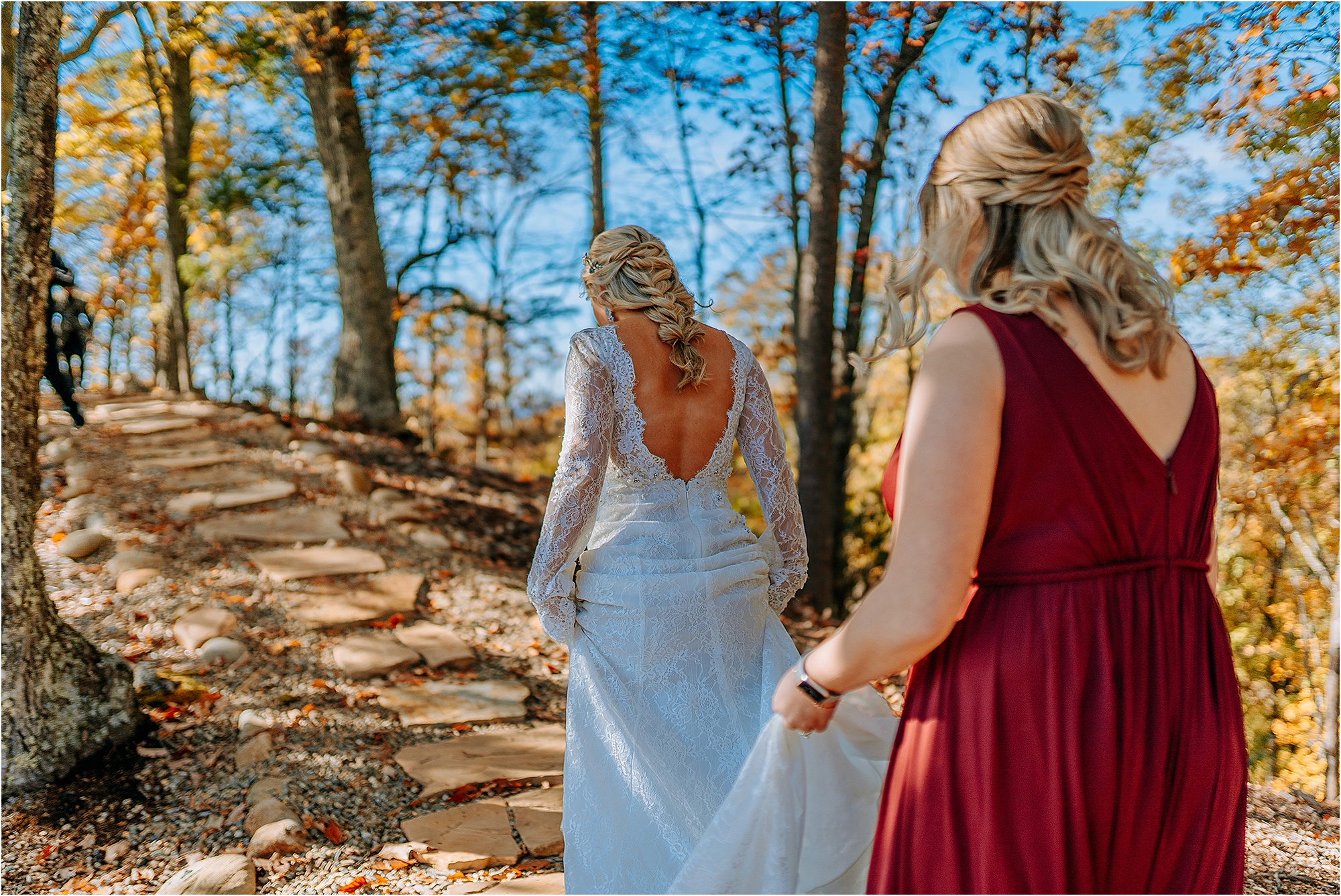 bride walking into woods with bridesmaid in burgundy dress