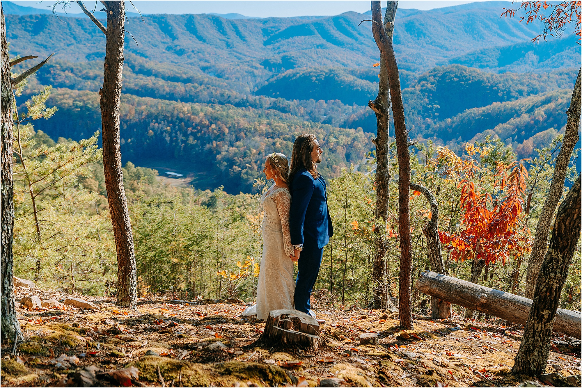 bride and groom standing back to back on mountaintop
