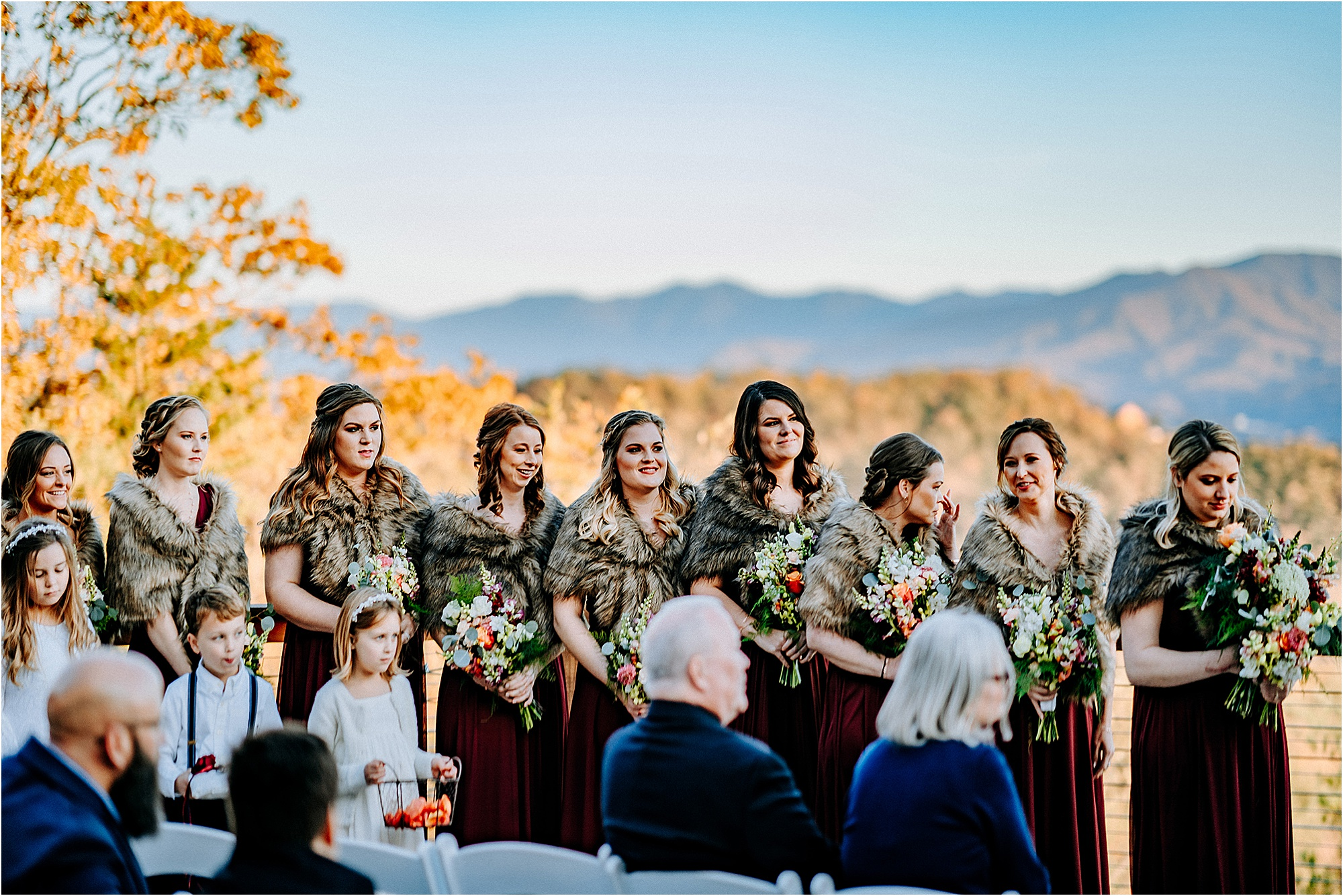 bridesmaids in burgundy dresses with faux fur