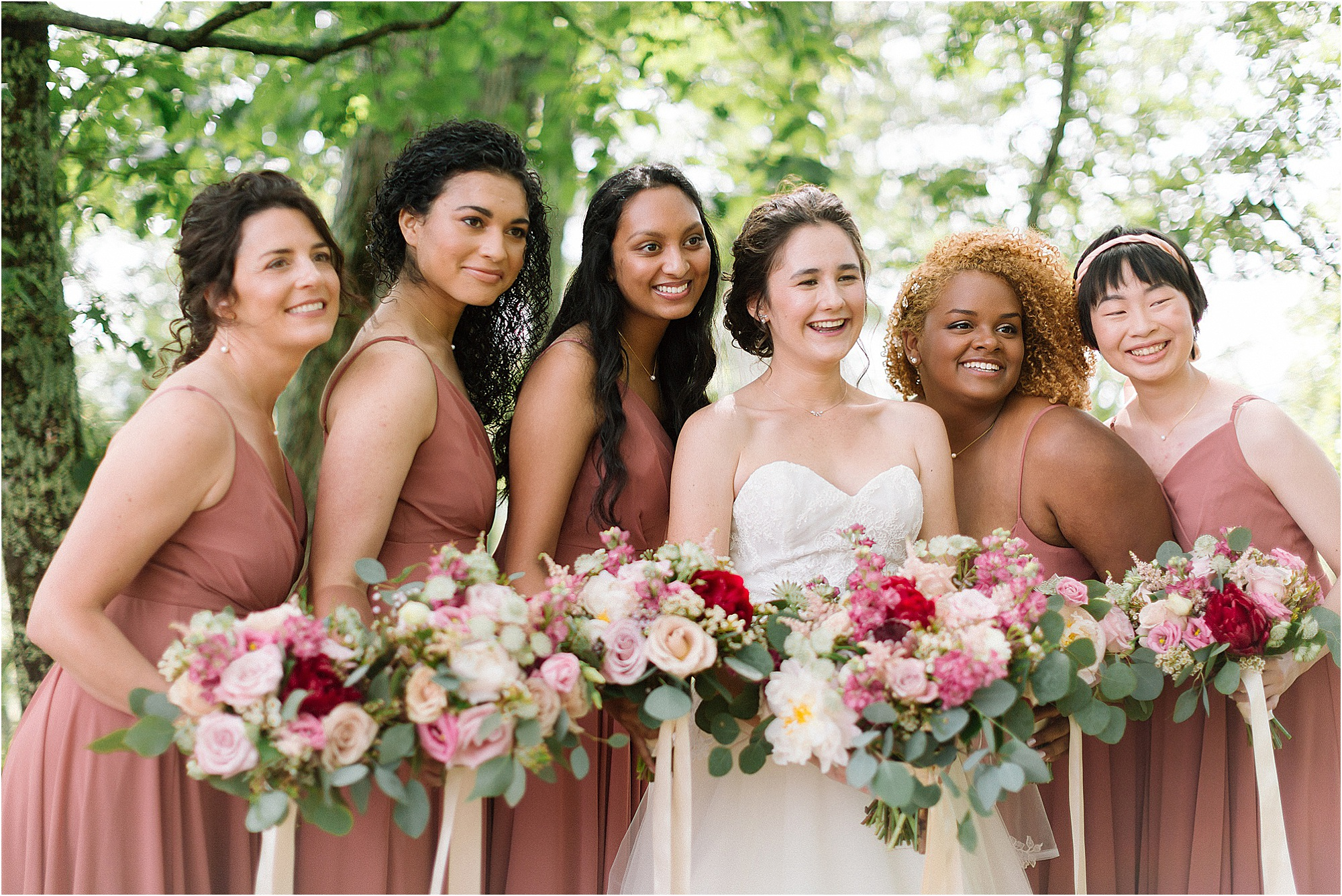 bride with bridesmaids in light pink wedding dresses