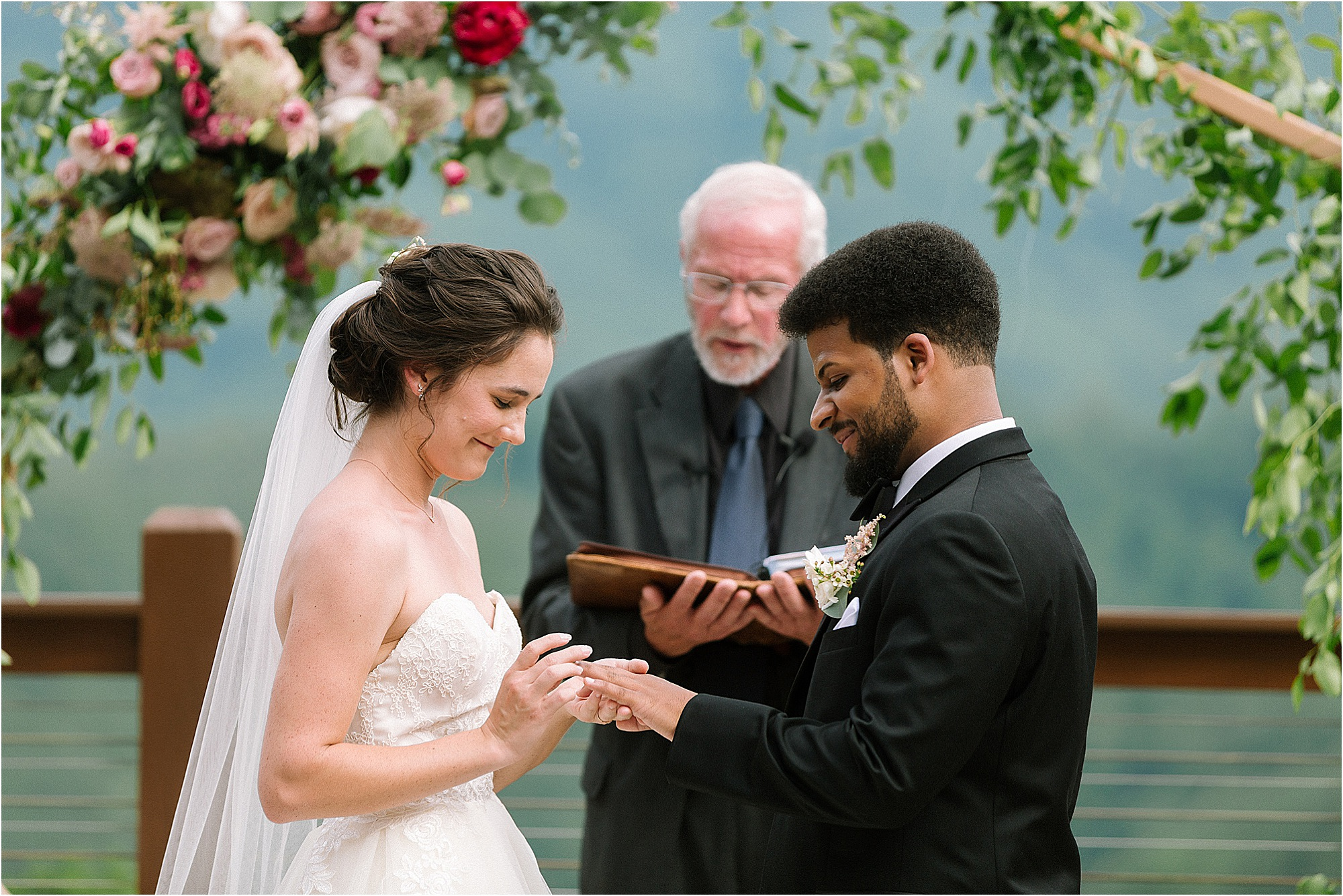 bride and groom exchange rings at wedding ceremony on mountaintop