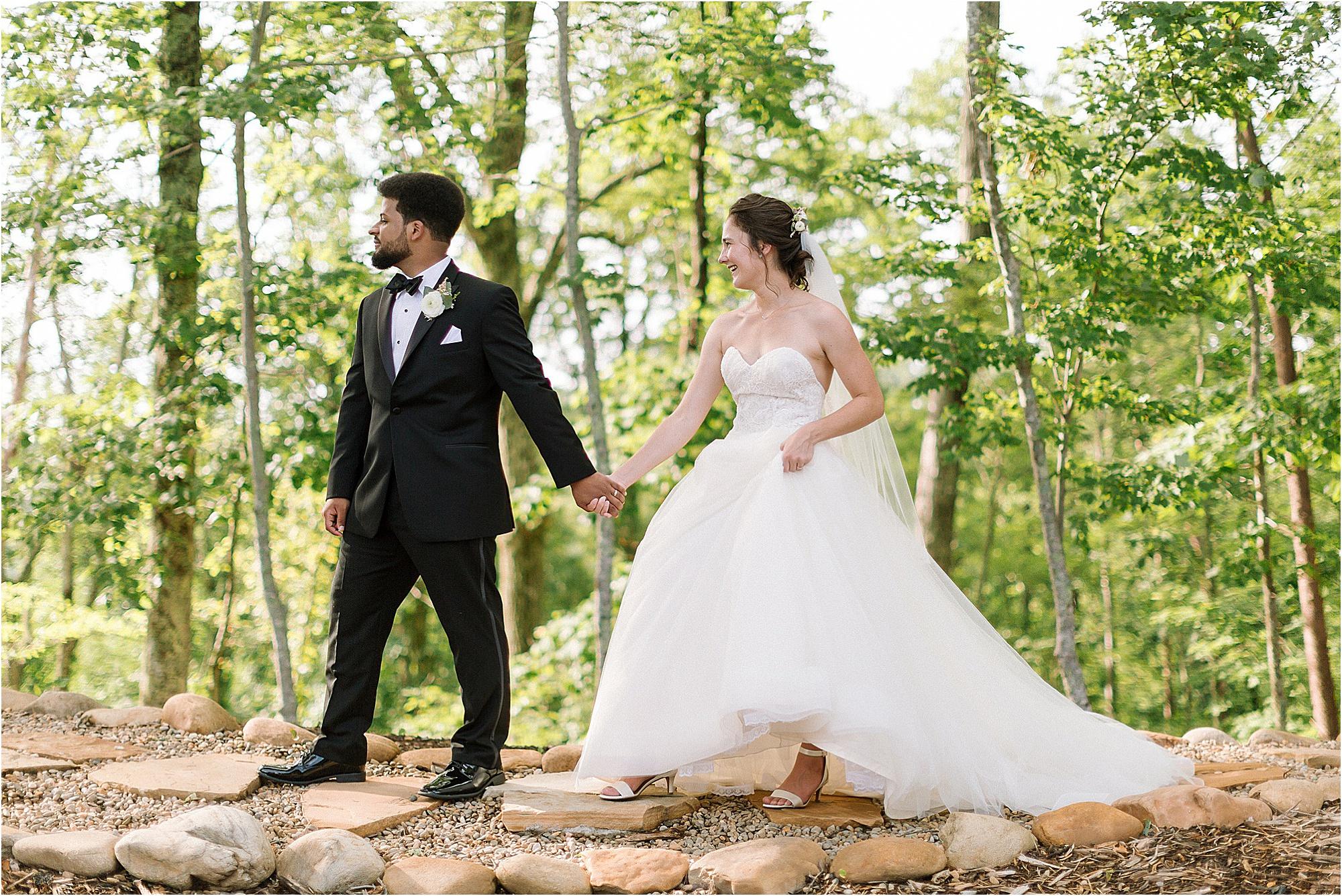 groom leads bride along path on mountaintop