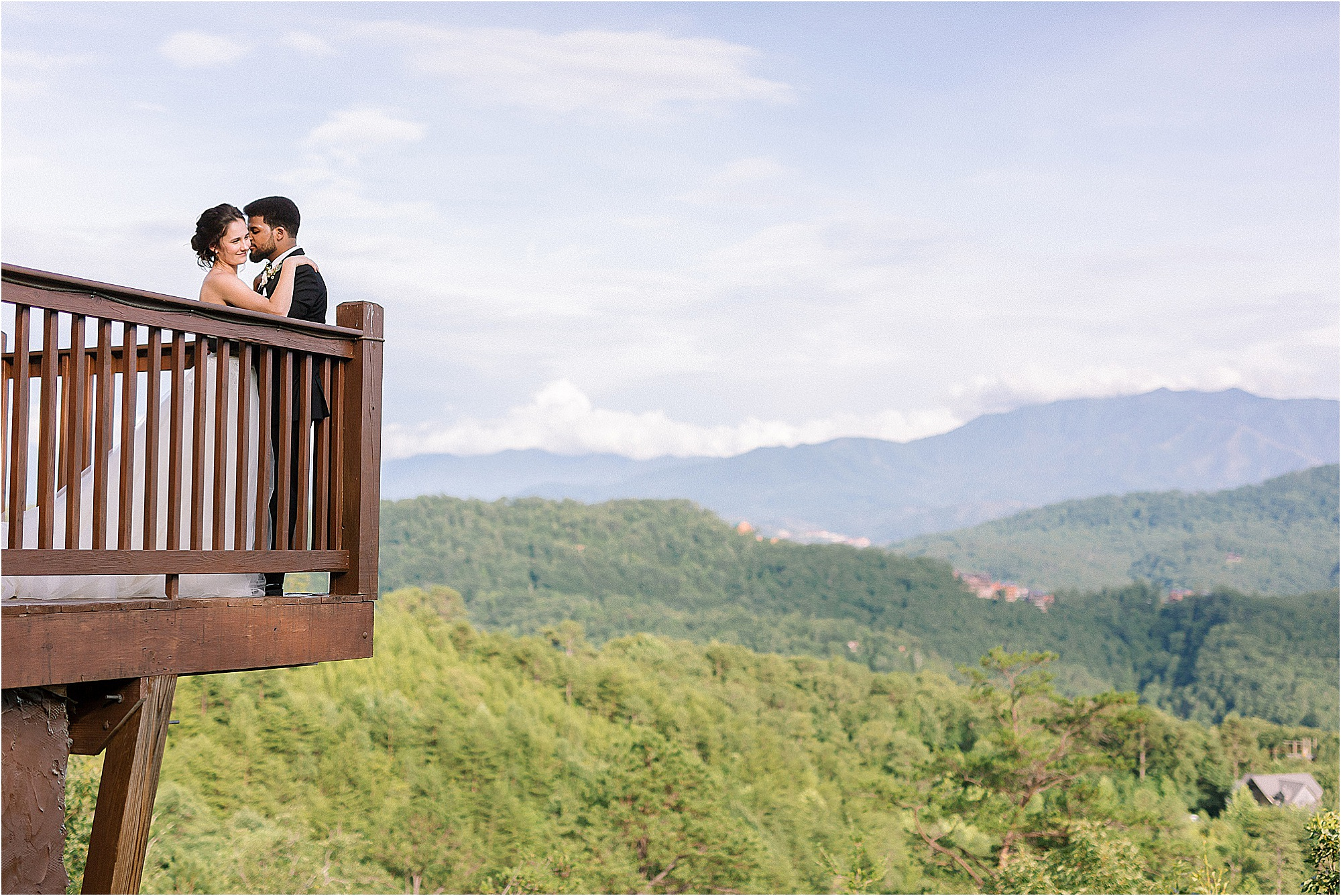 man and woman kiss on balcony overlooking mountains