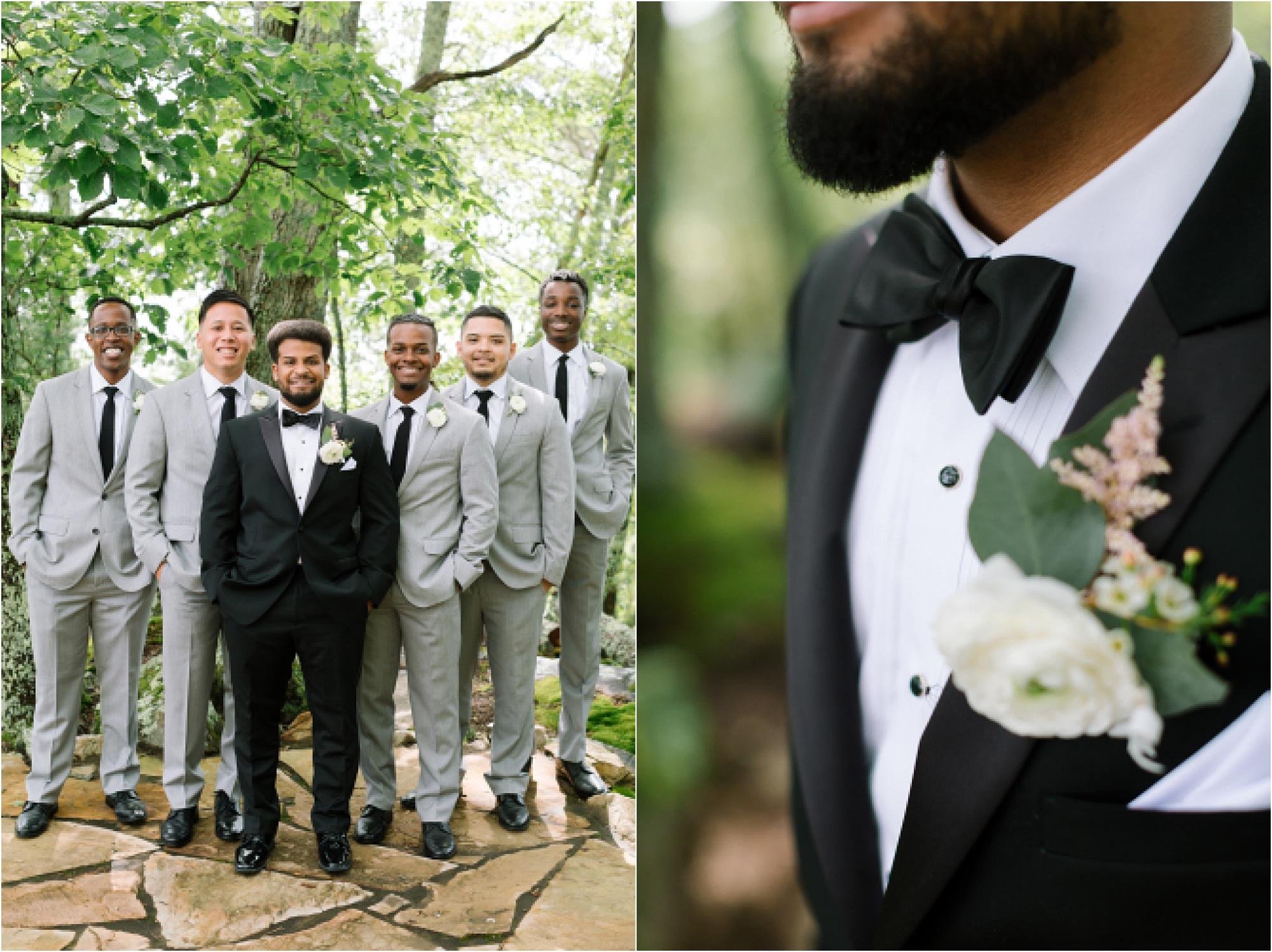 groom in black suit with groomsmen in gray suits