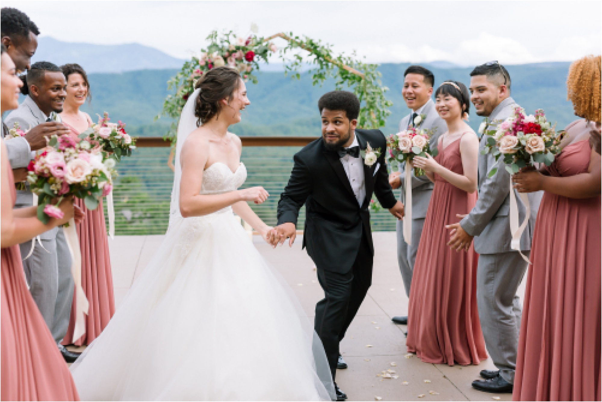 bride and groom walk between bridal party
