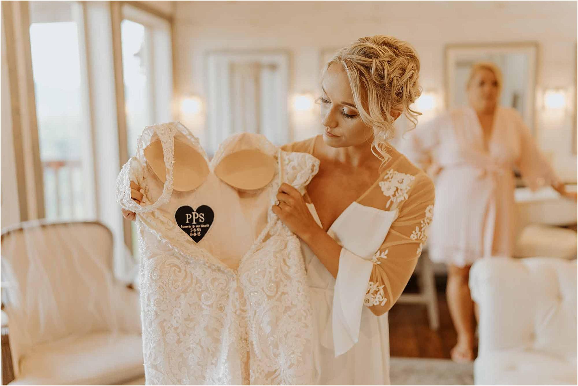 bride holding up wedding dress with stitched heart inside