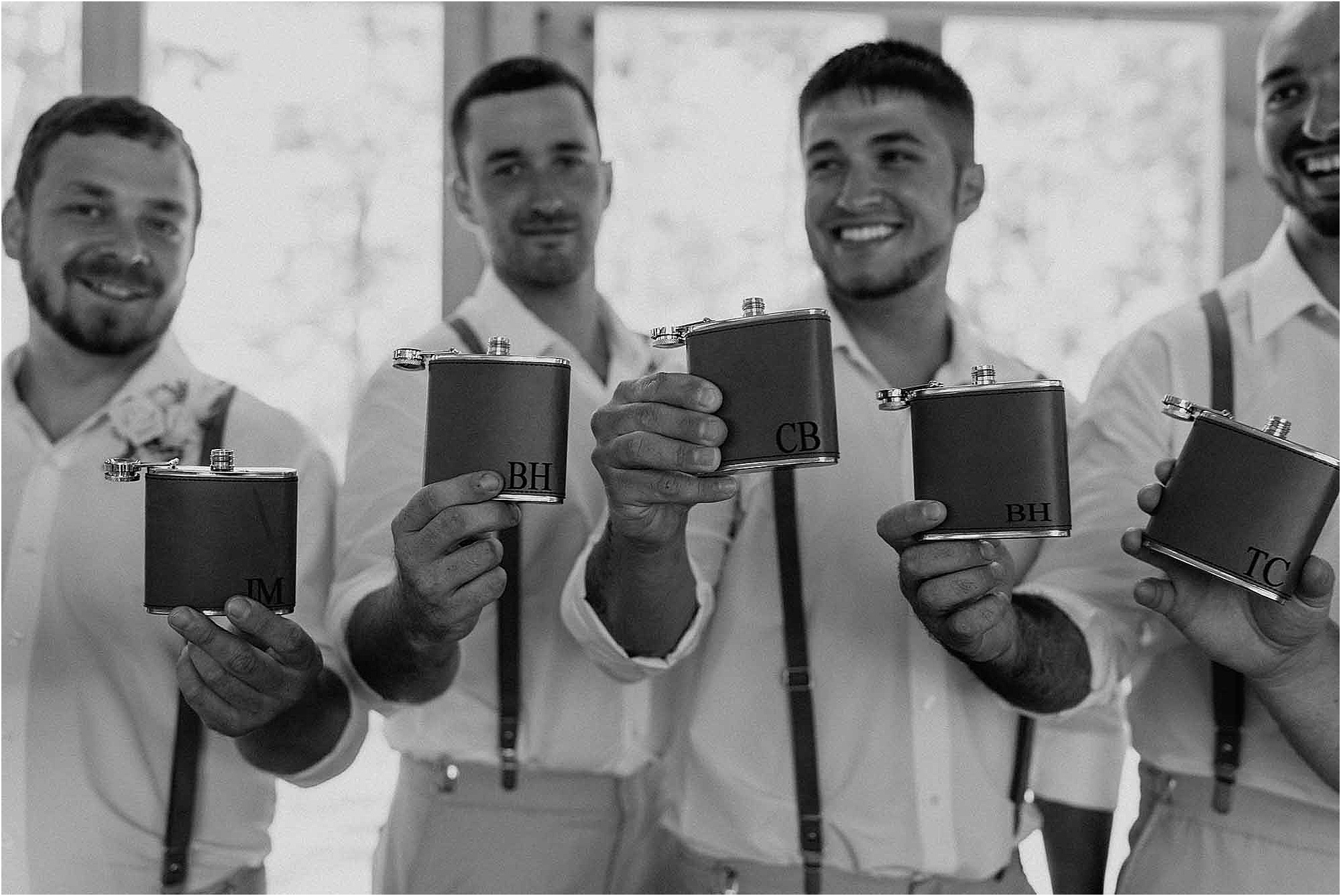groom and groomsmen holding up personalized flasks