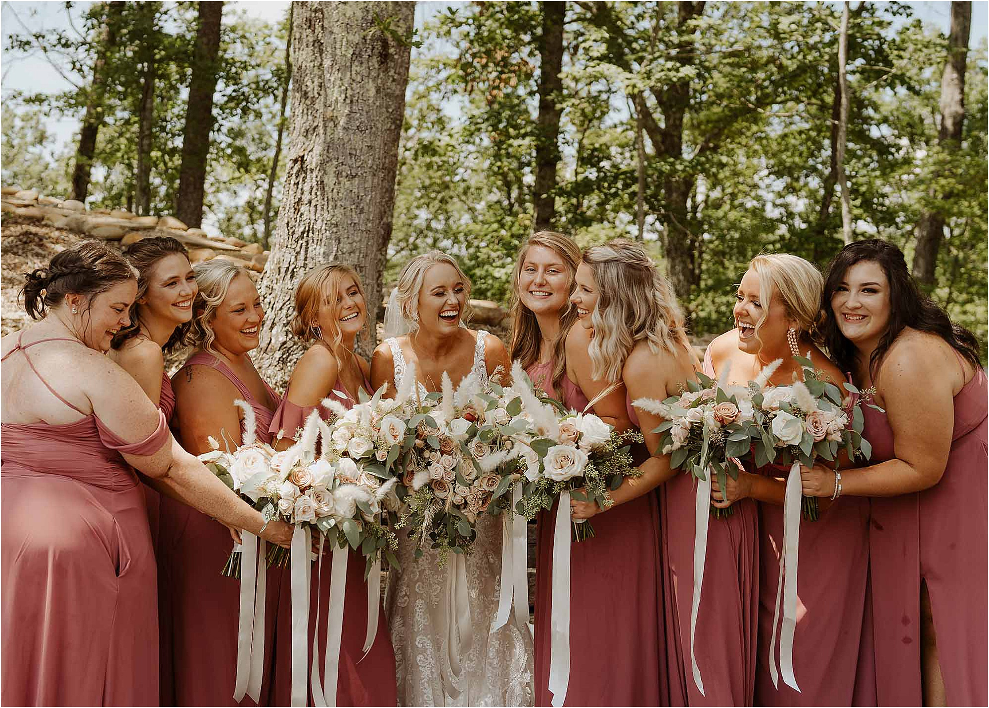 bride and bridesmaids laughing while holding bouquets