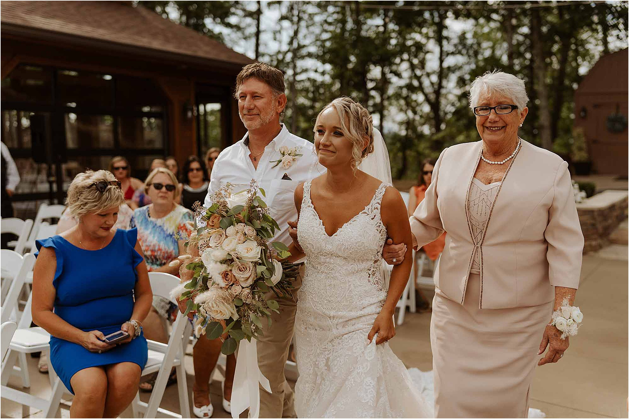 bride walking down aisle with mother and father at summer wedding