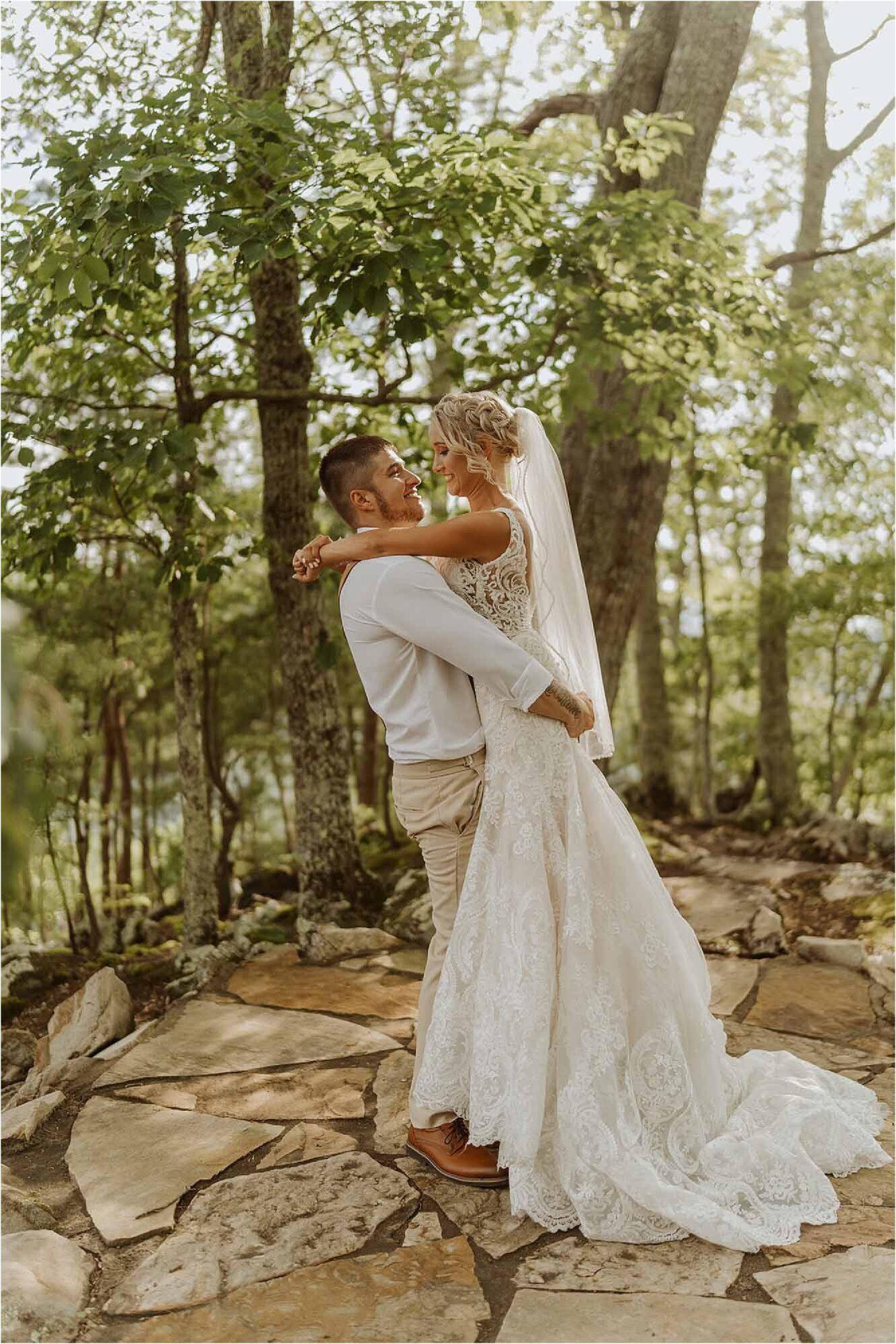 groom lifting up bride in woodland scene