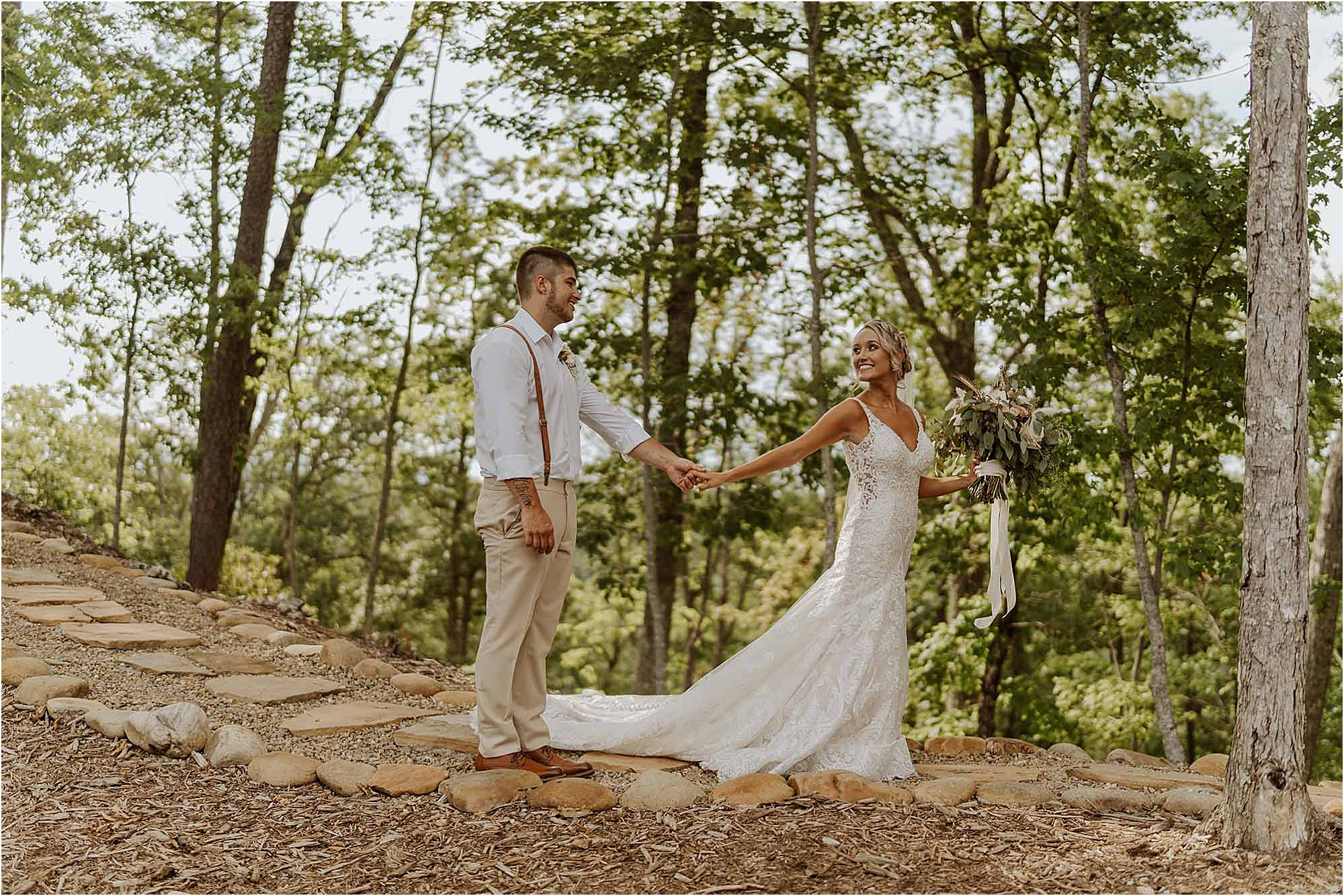 bride leading groom down forest path