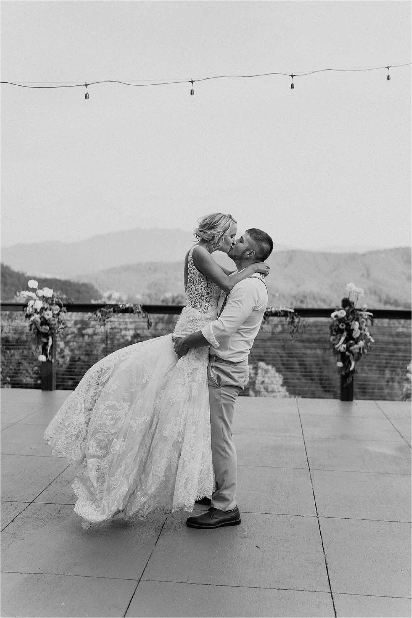 groom lifting up bride on mountainside patio