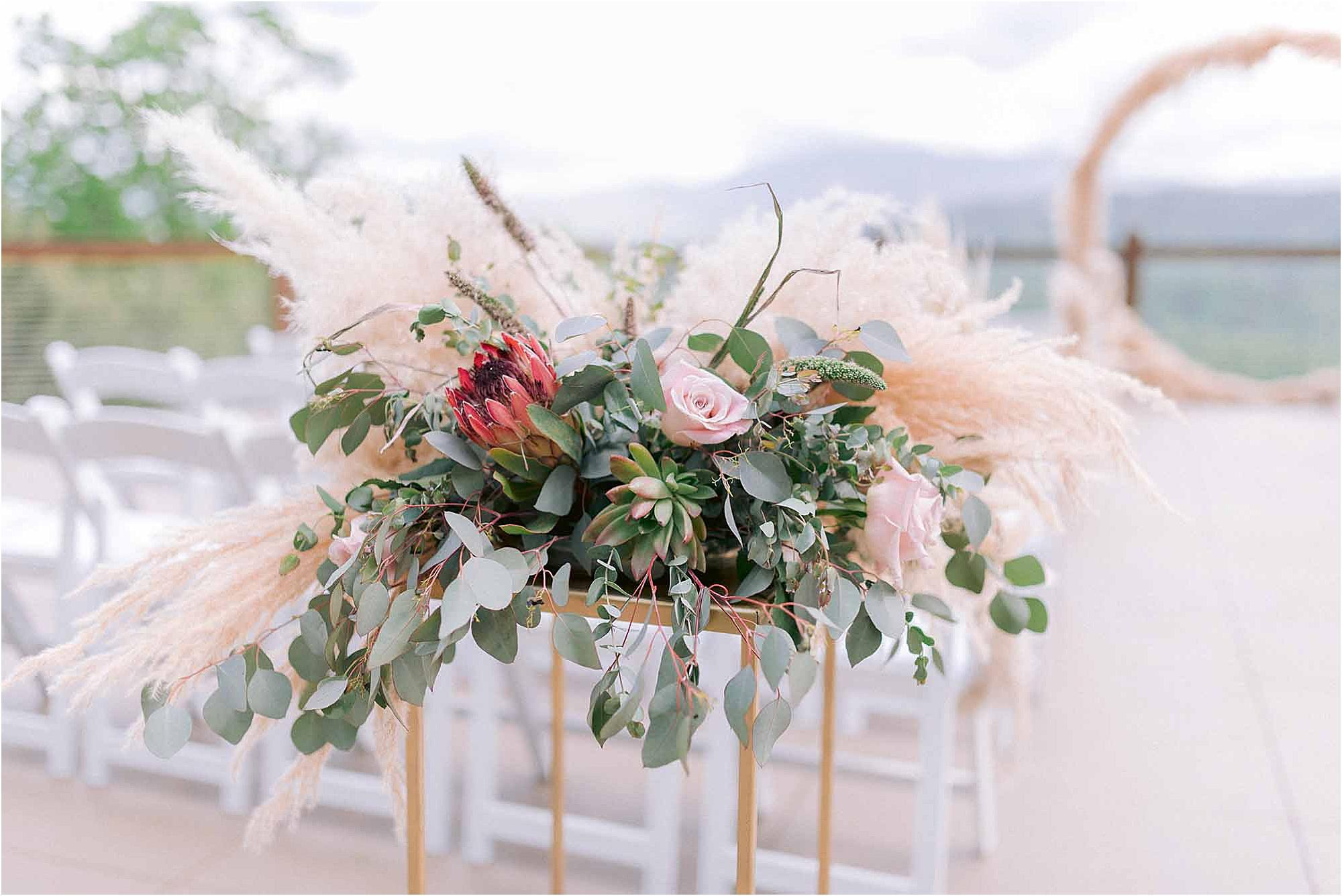 pink and gold flower arrangement at wedding ceremony