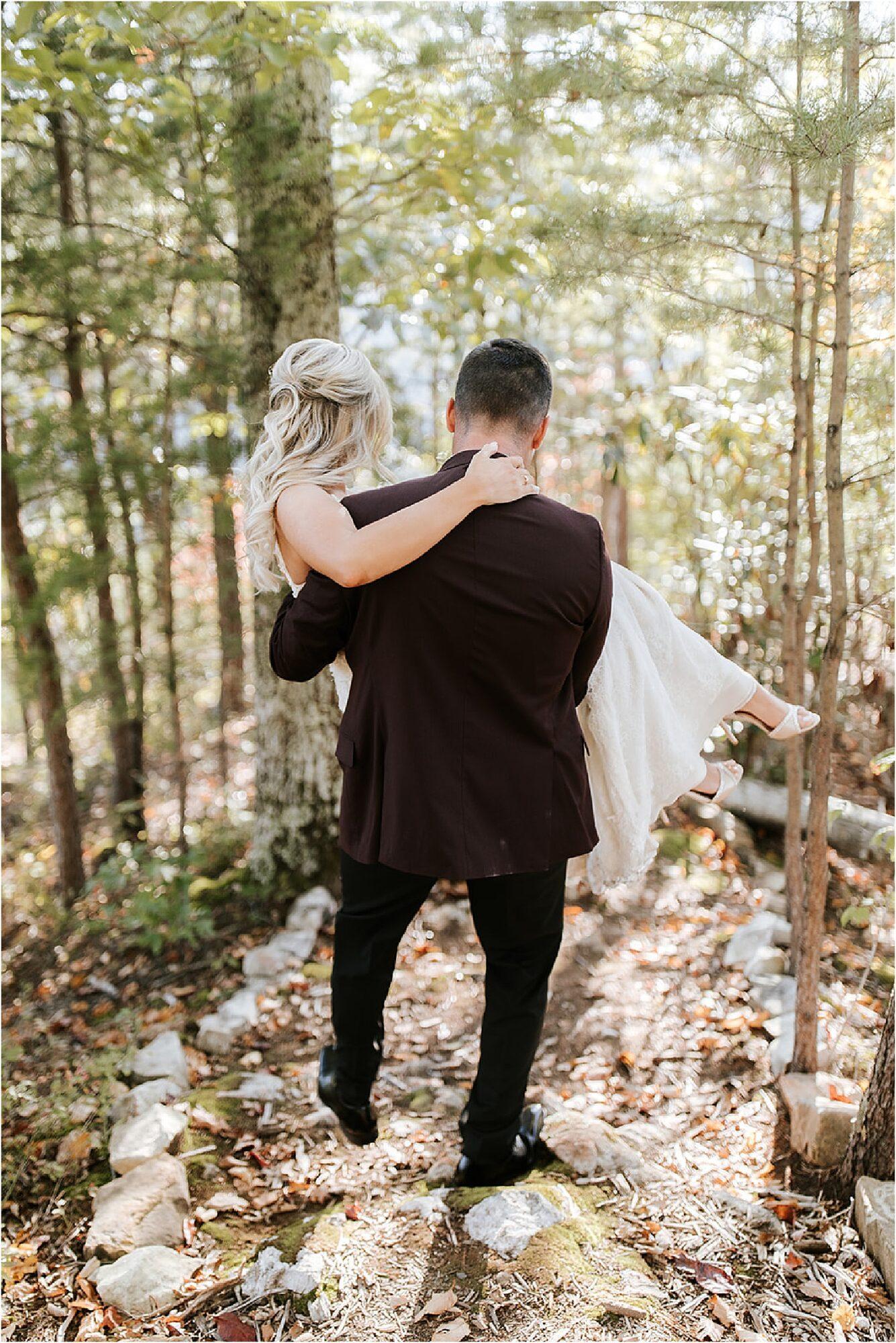 groom carrying bride in the woods