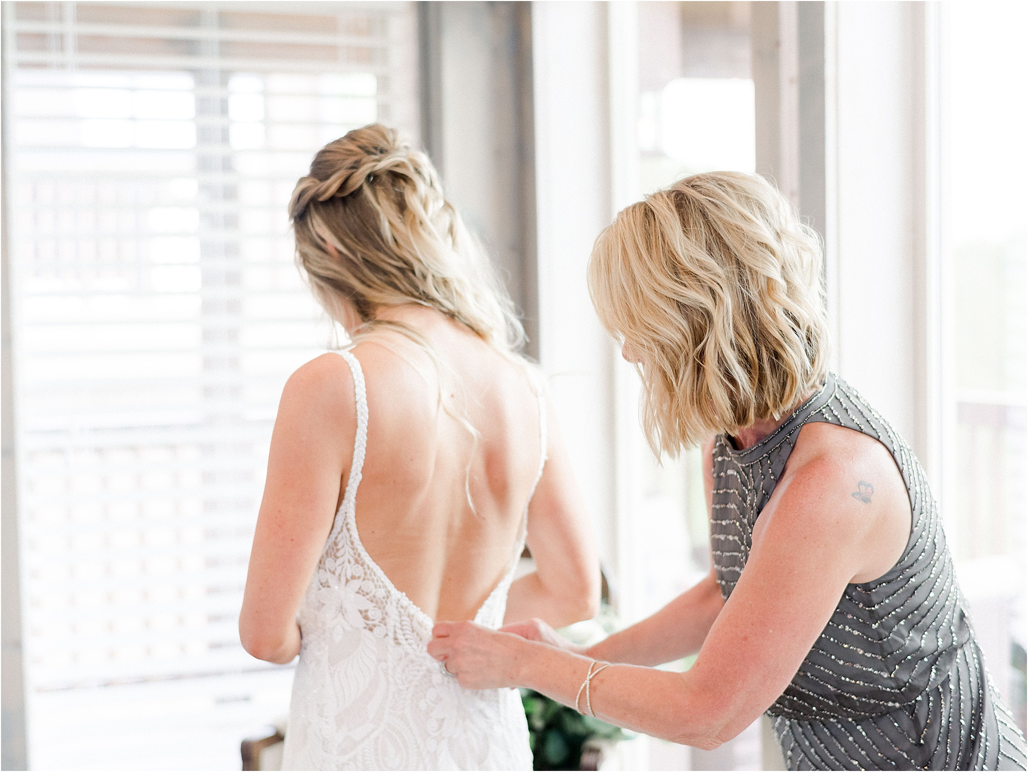 mother of the bride helping bride into wedding dress
