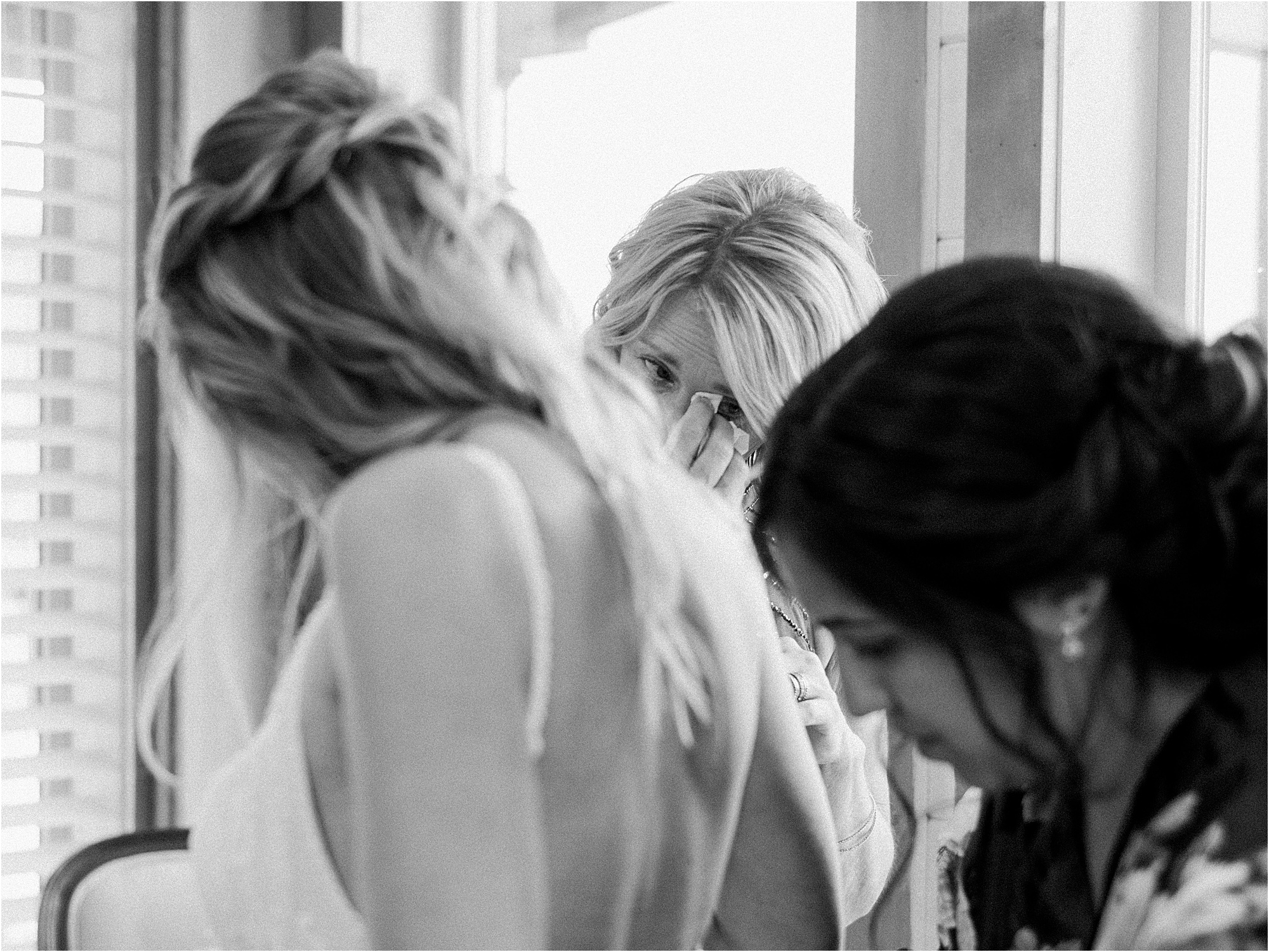 mother of the bride crying while bride gets into wedding dress