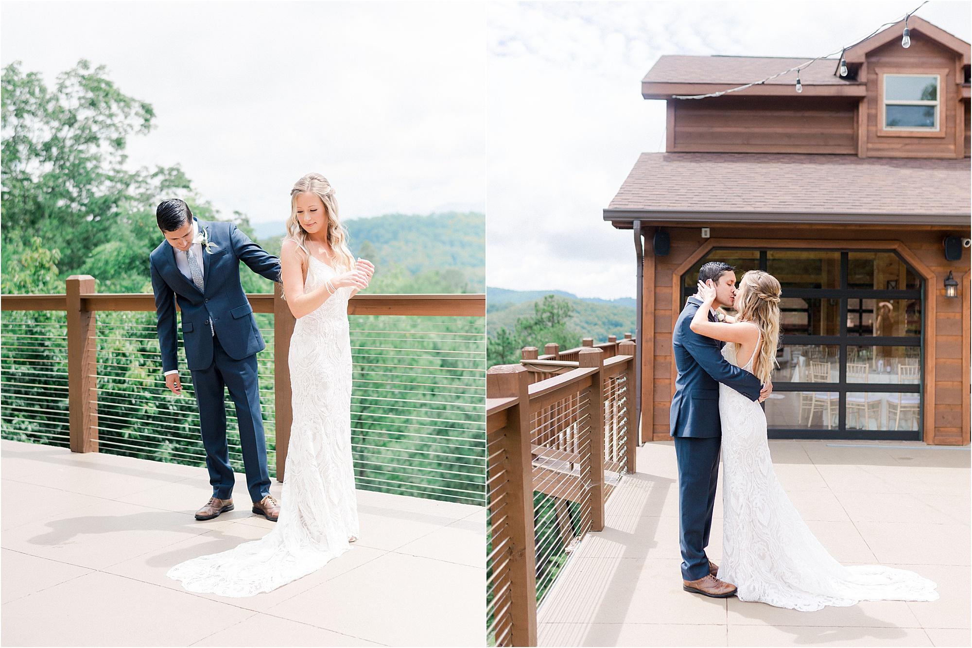 groom and bride kissing at railing at mountain wedding cabin