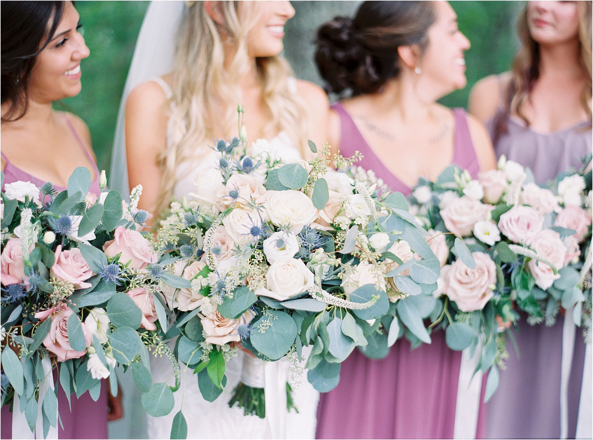 bride and bridesmaids in lilac dresses holding lush wedding bouquets