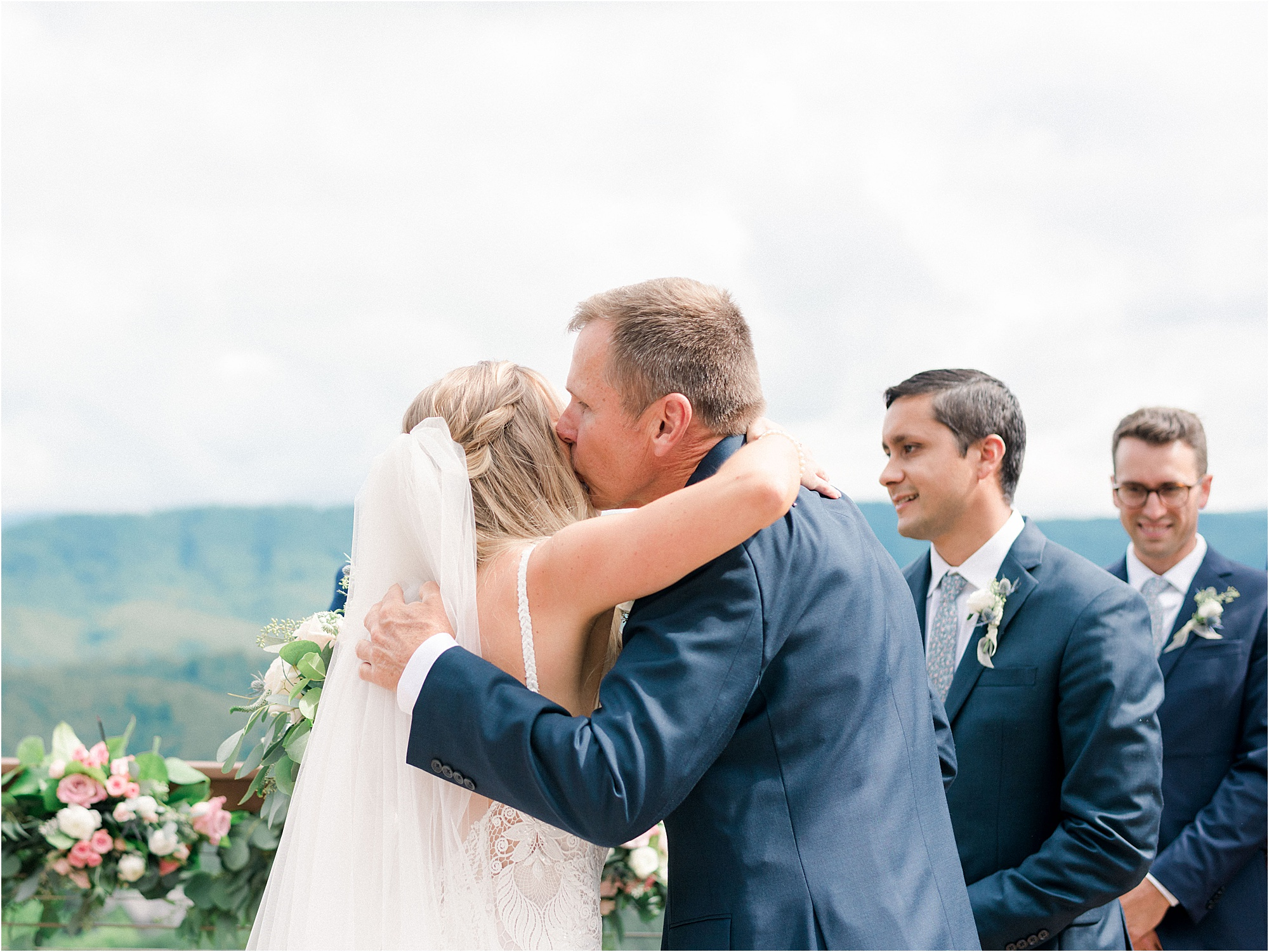 father hugs daughter at wedding ceremony