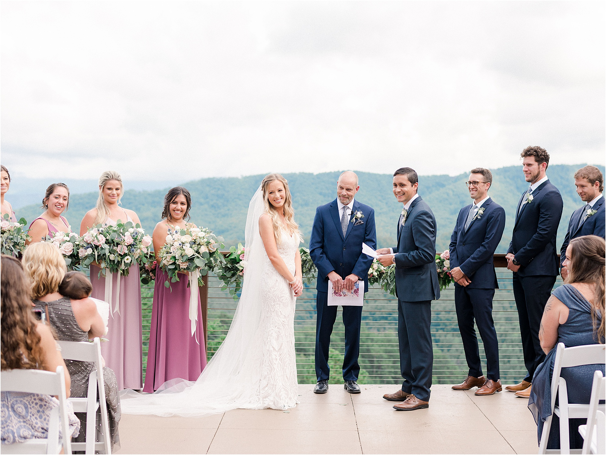 bride and groom laugh while reading vows overlooking the Smokies