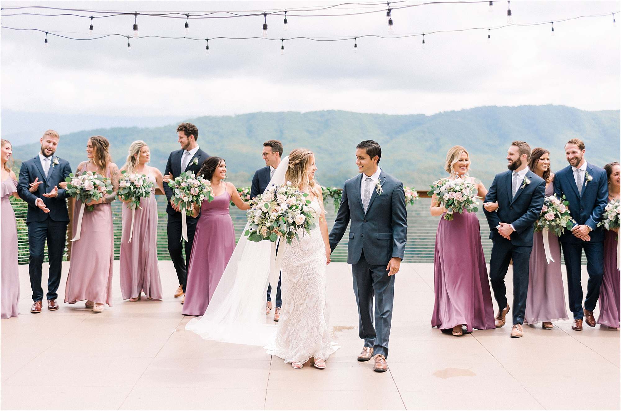 bride and groom walk with bridal party in blue suits and purple bridesmaid dresses