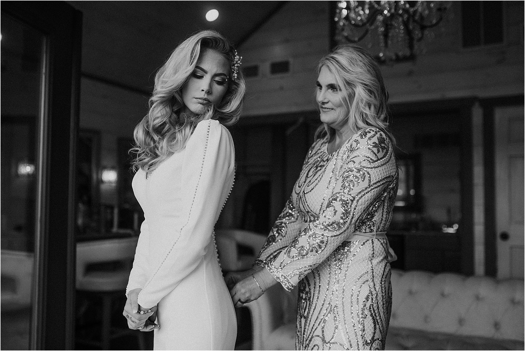 bride getting into wedding dress with mother