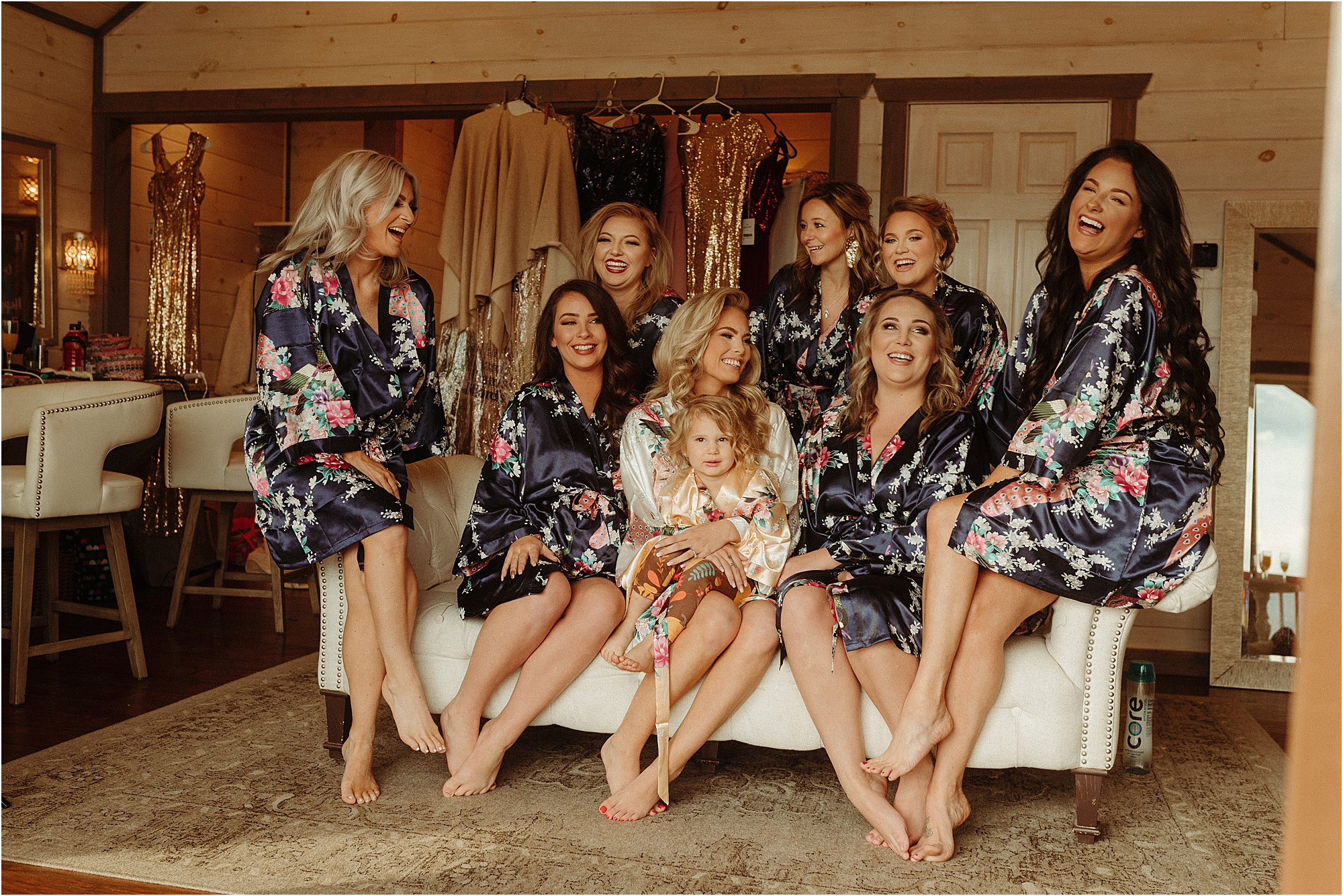 bride sitting on couch wearing robes with bridesmaids