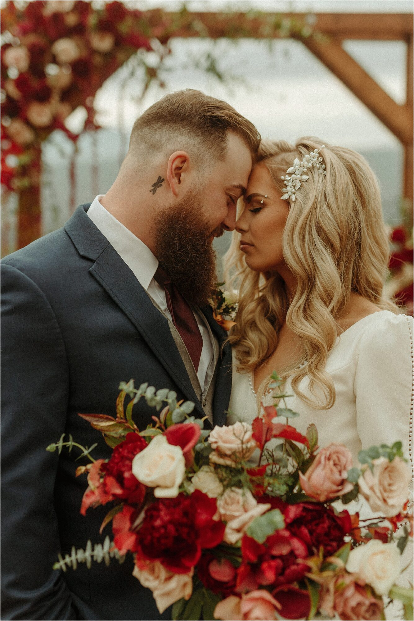 man and woman touch foreheads together while holding large jewel tone bouquet