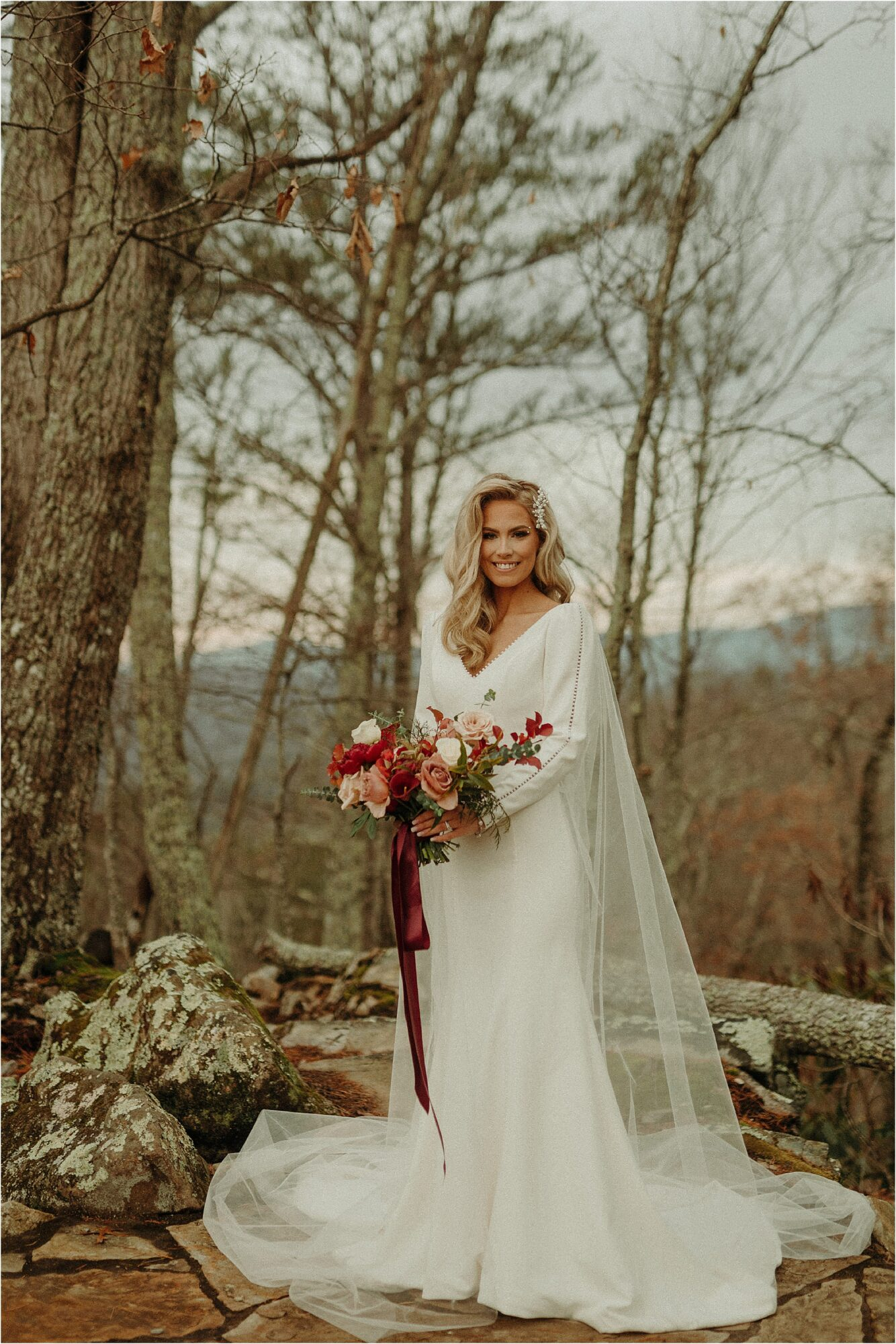 bride standing in woods wearing long white edgy gown with sleeves and sheer cape