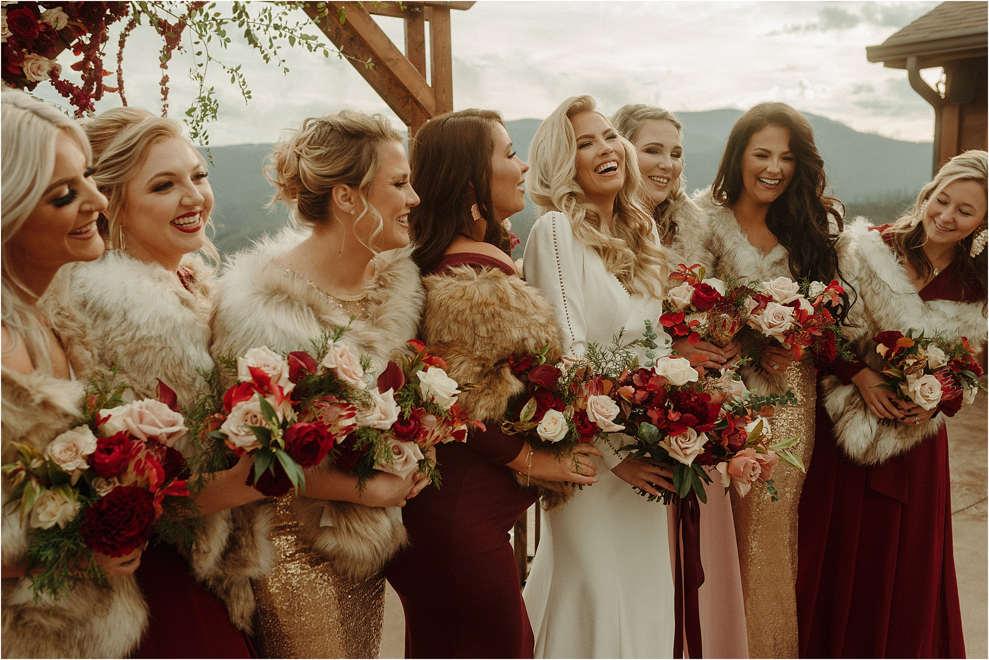 bride laughing with bridesmaids wearing faux fur shawls