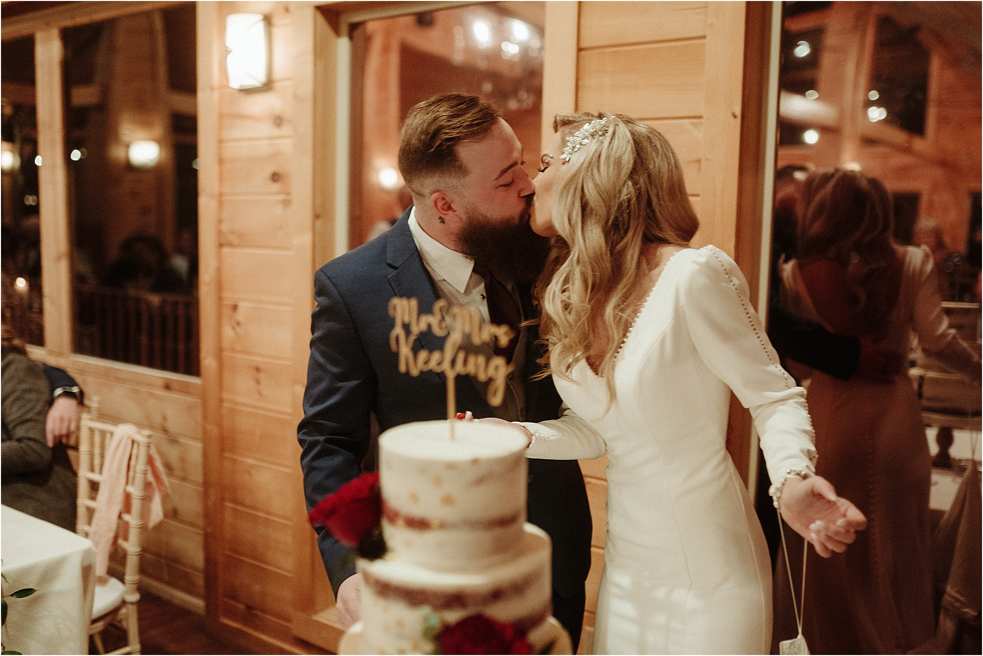 bride and groom kiss at cake cutting