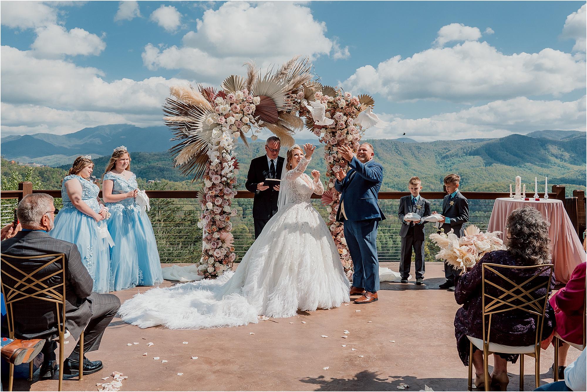 bride and groom wedding under dried floral wedding arch