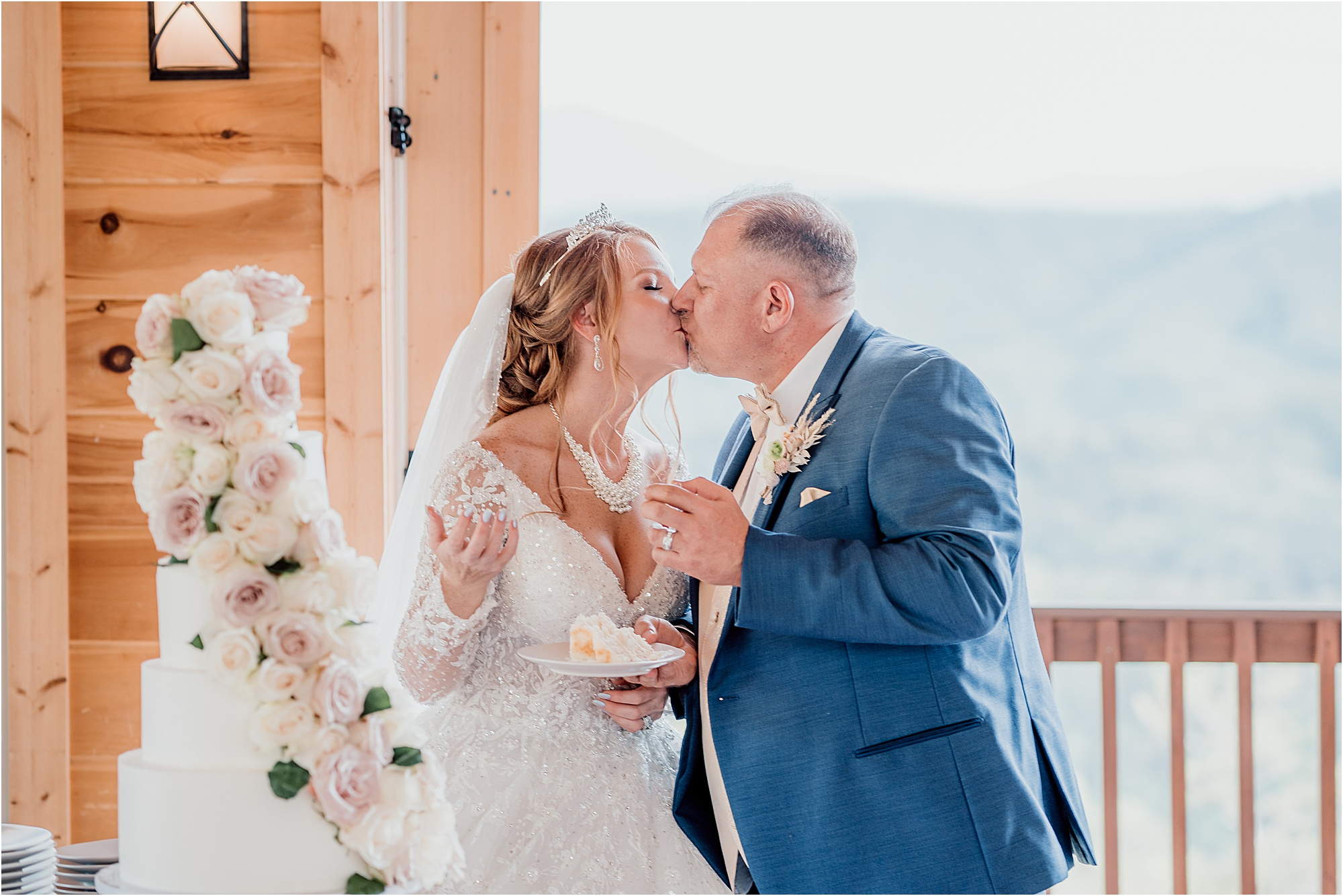 bride and groom kiss after cutting wedding cake