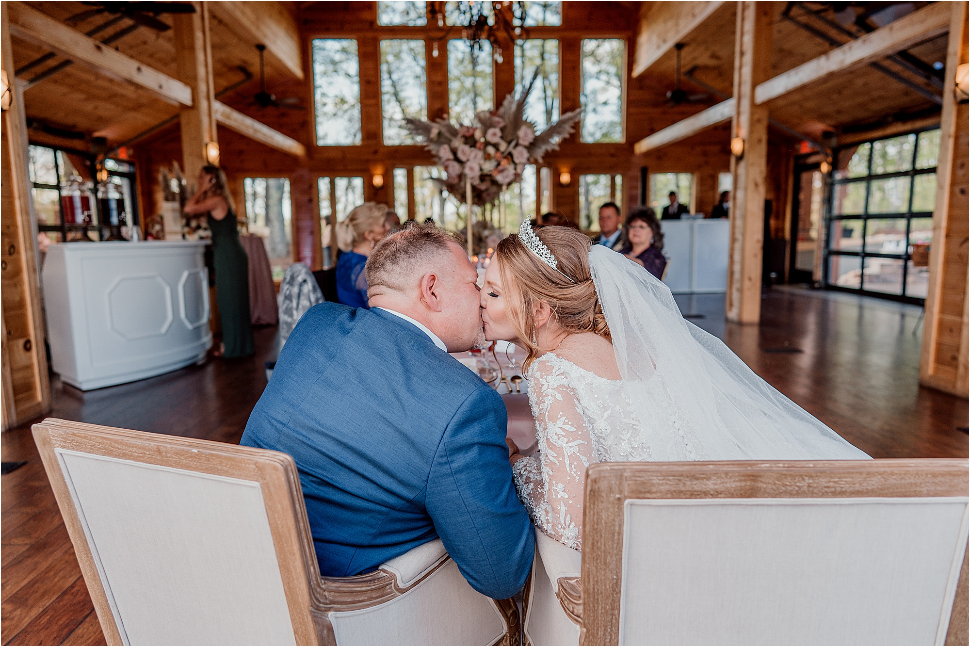 bride and groom kiss while sitting in wedding chairs