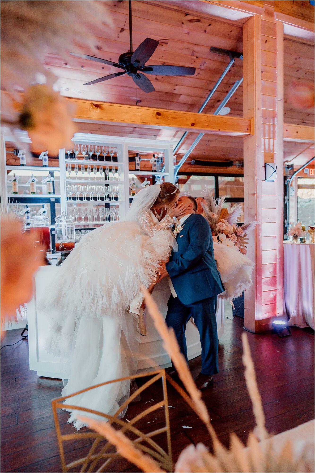bride and groom kiss on bar top