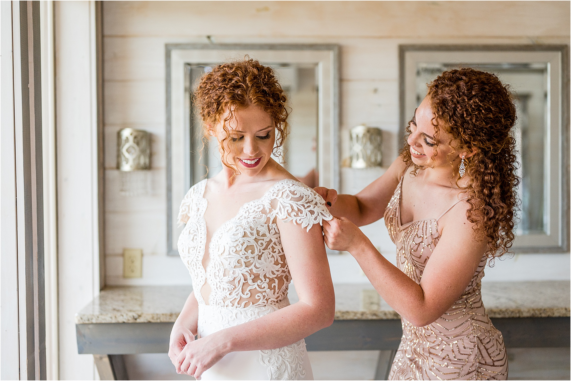 sister of the bride helping bride into dress