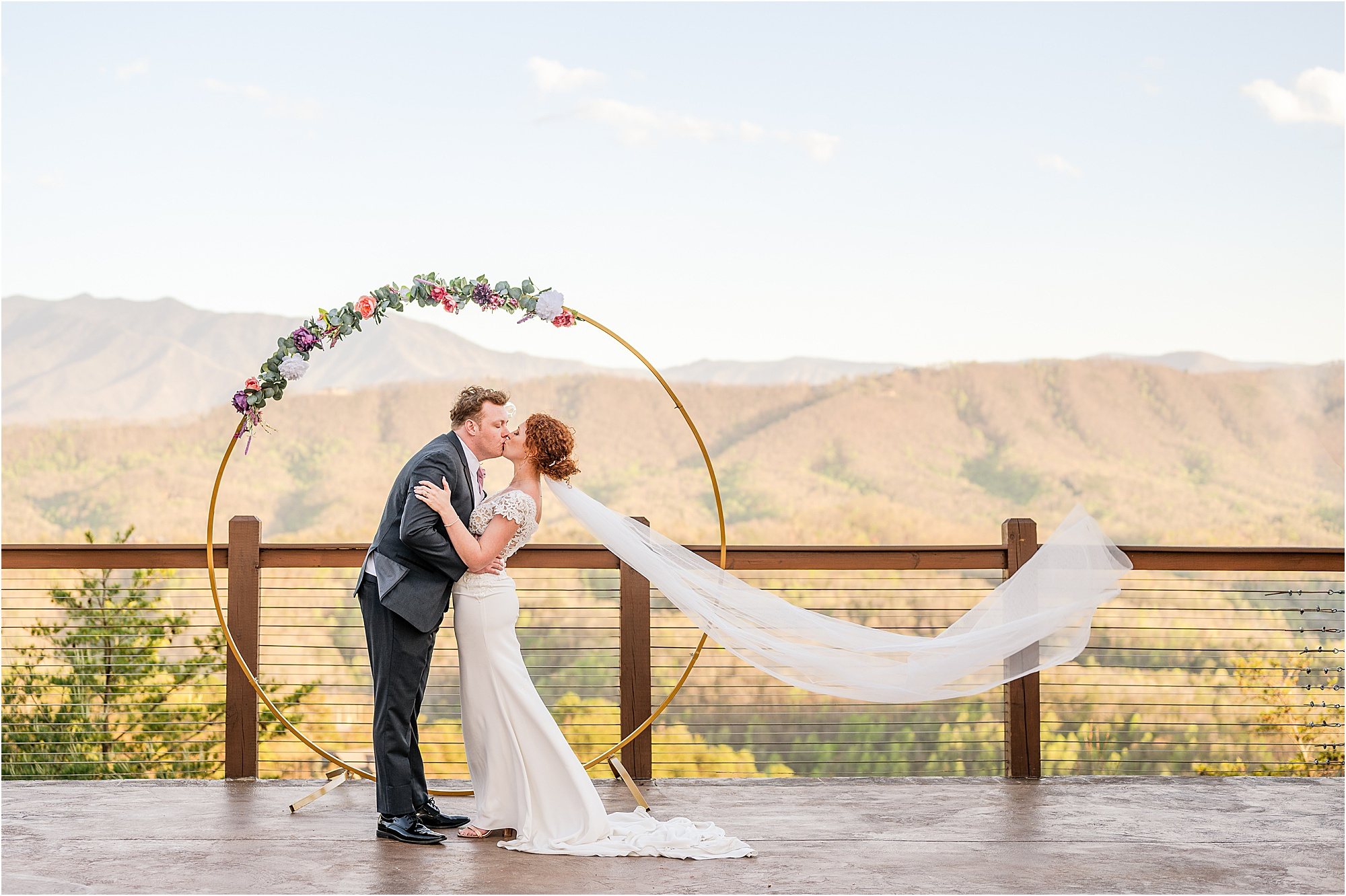 groom dips bride infront of circle wedding arbor with veil blowing in the wind