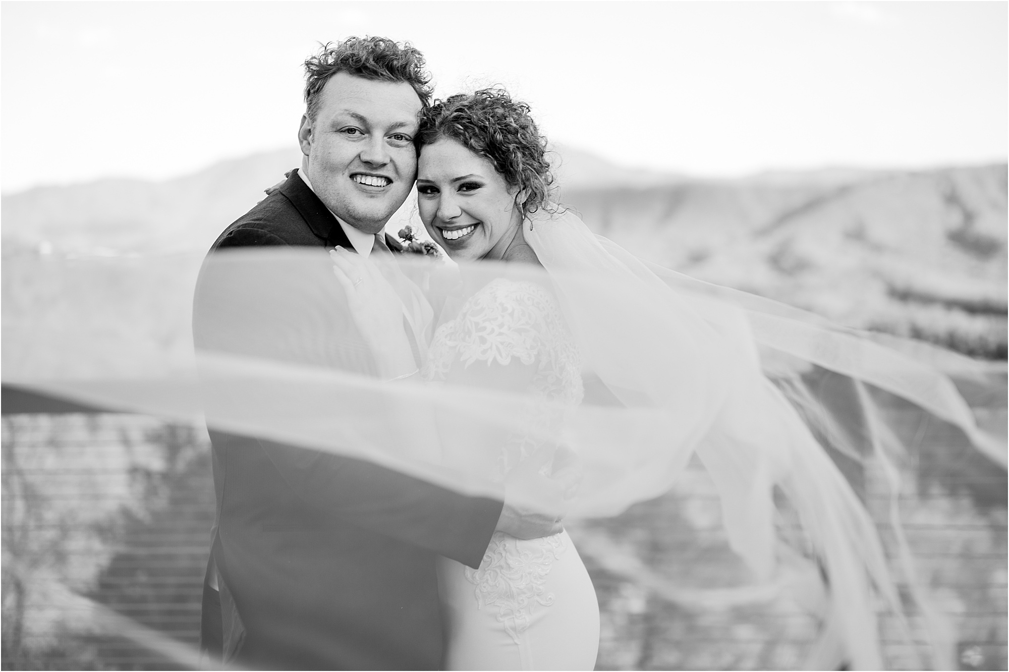 black and white portrait of bride and groom with veil blowing in the wind