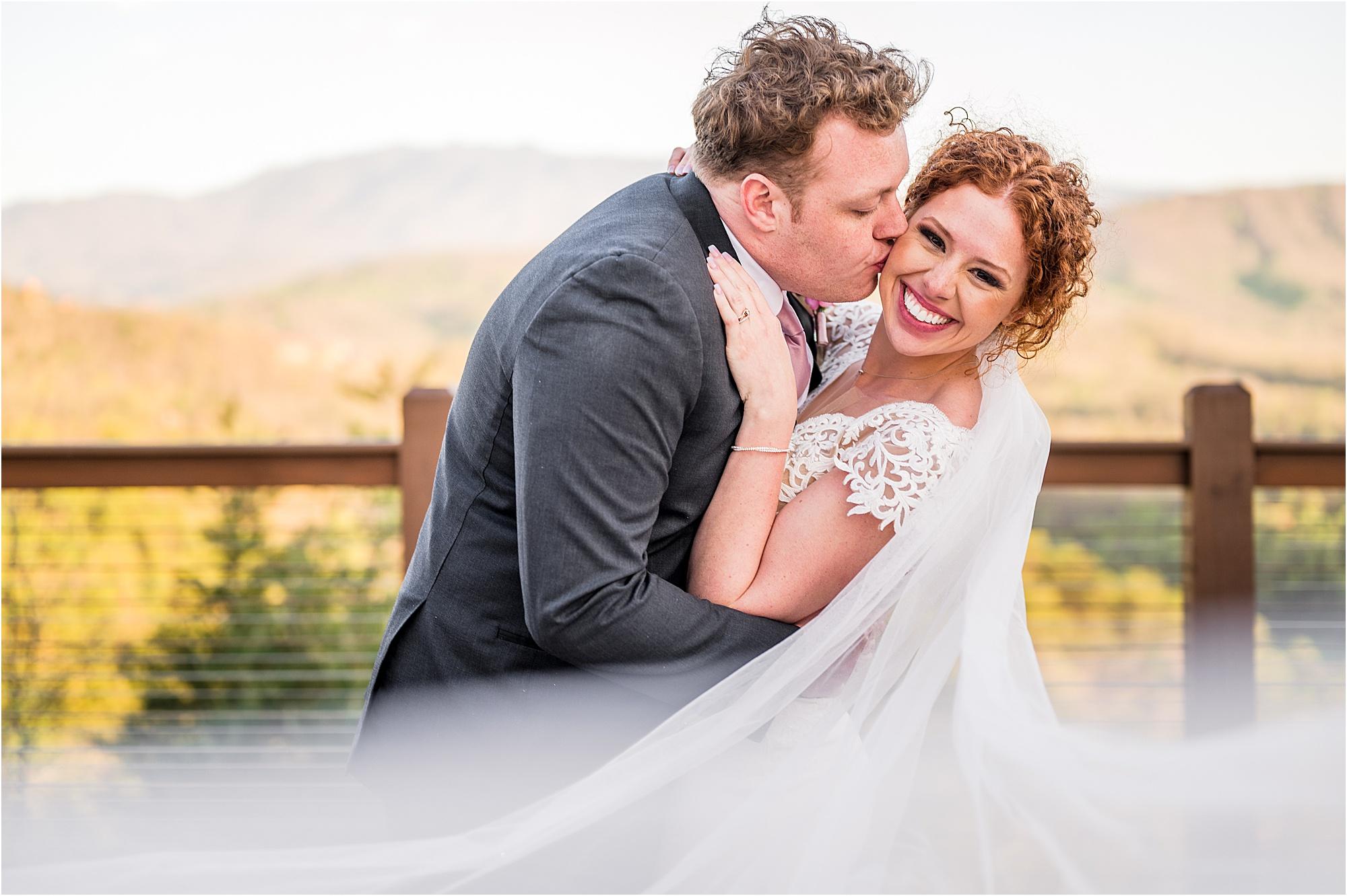 groom kisses bride on cheek as he dips her backwards