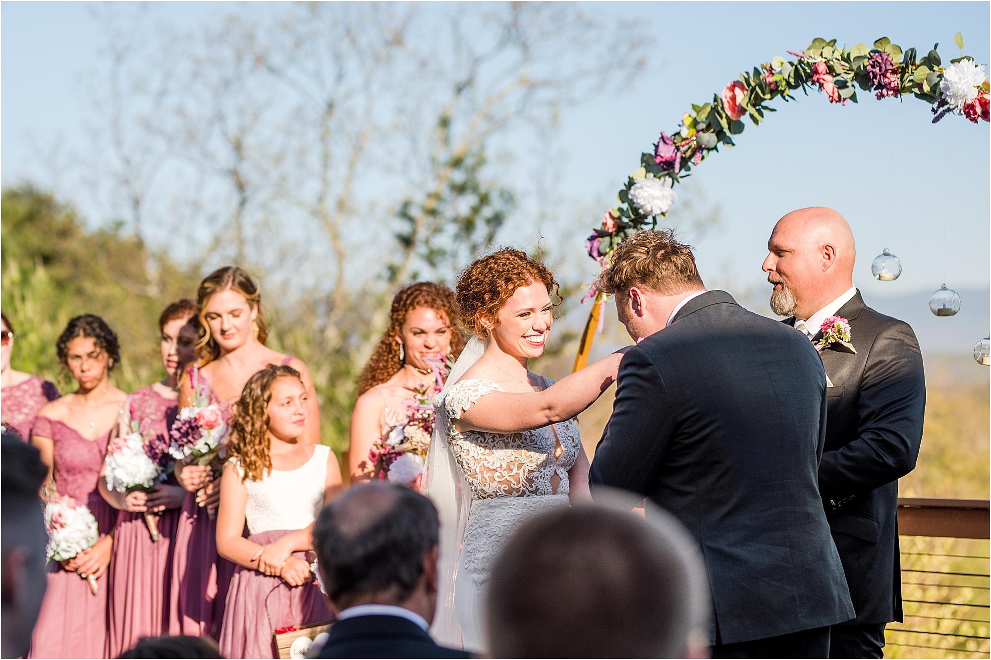 groom kisses bride's hand at wedding ceremony