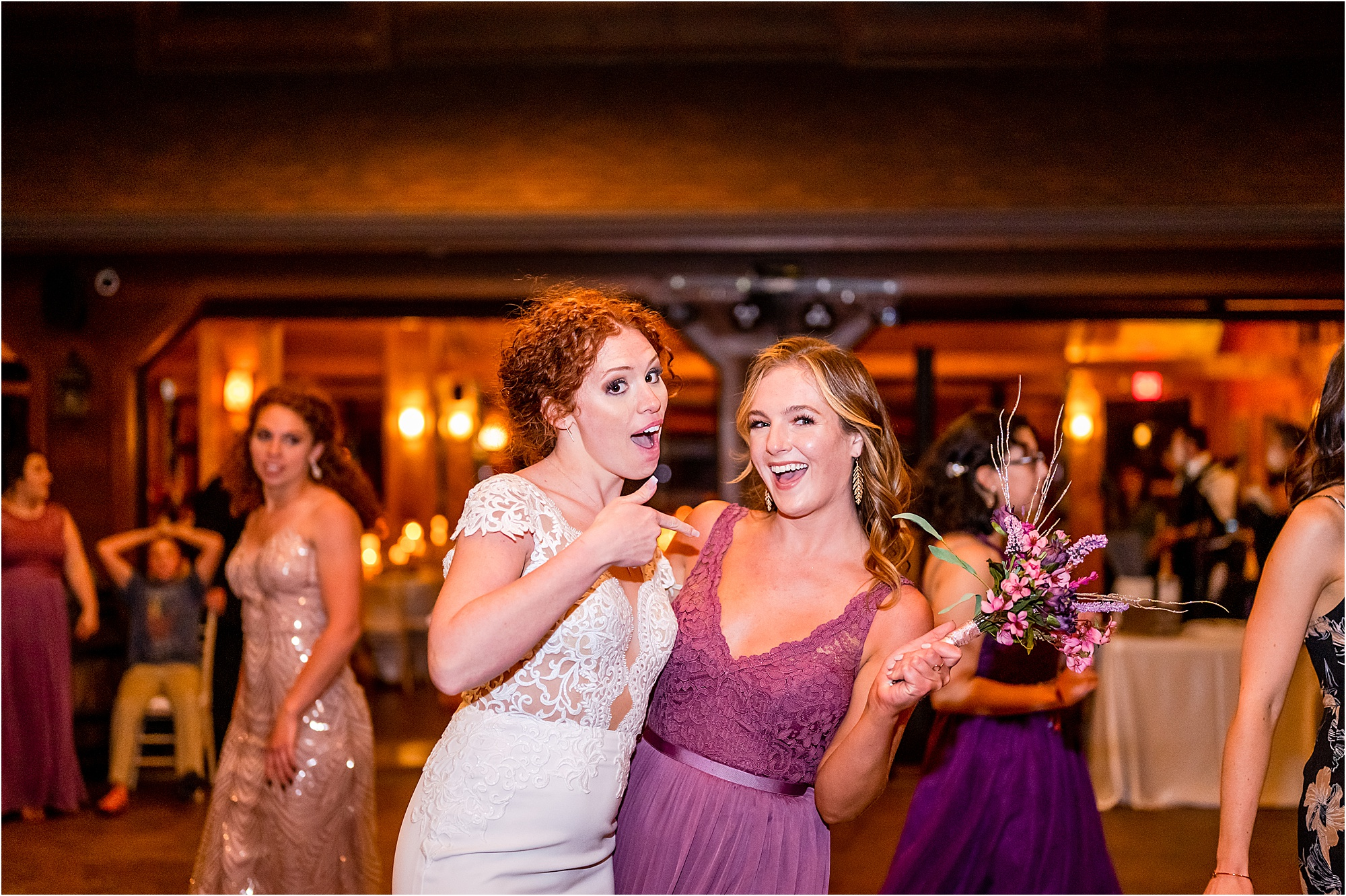 bride and bridesmaid pose for photo with wedding bouquet
