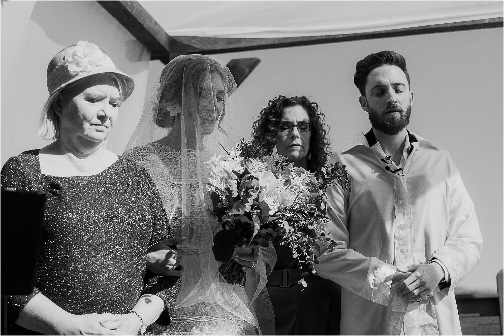 bride and groom standing under Jewish Wedding Canopy