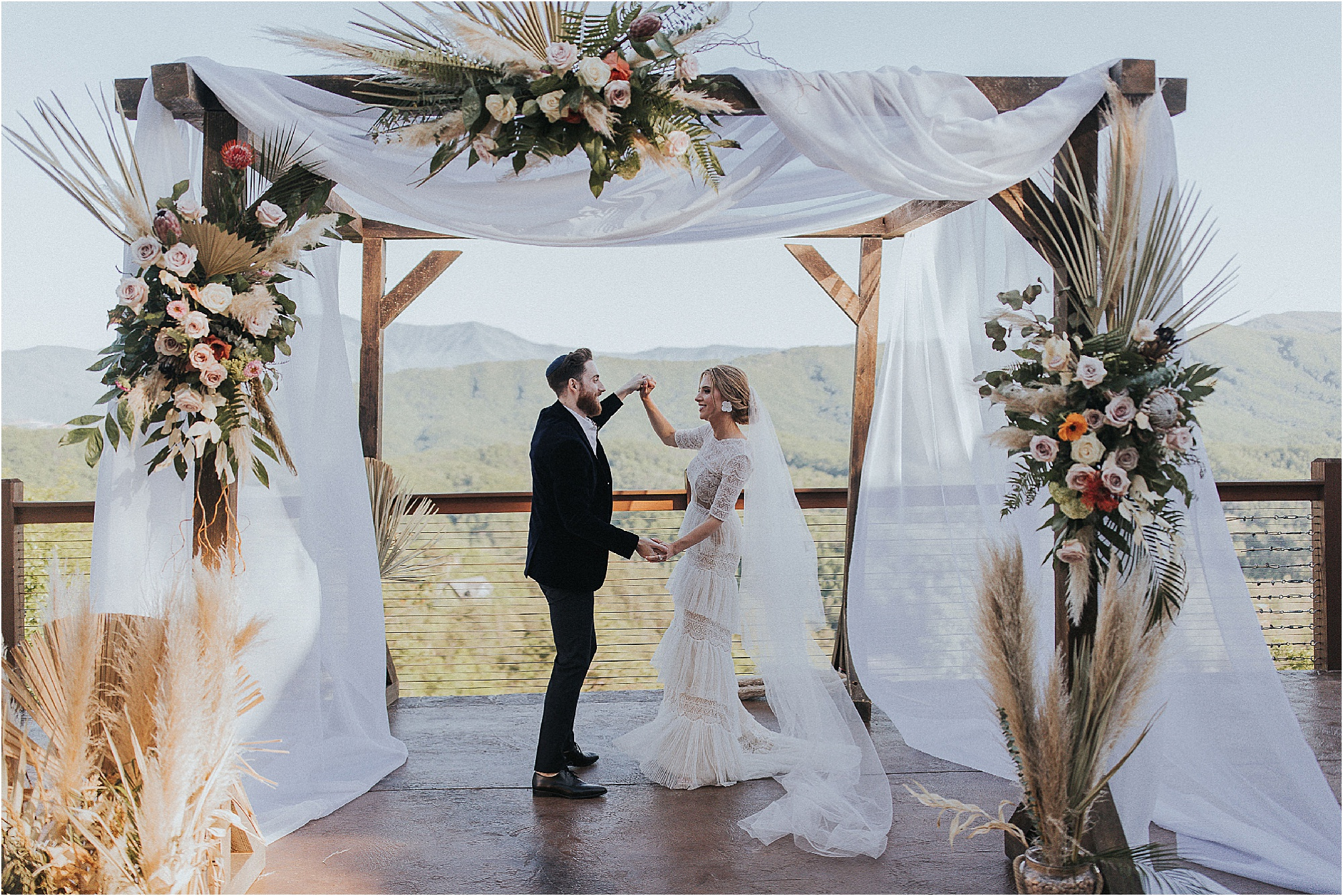 bride and groom dancing under white Huppah