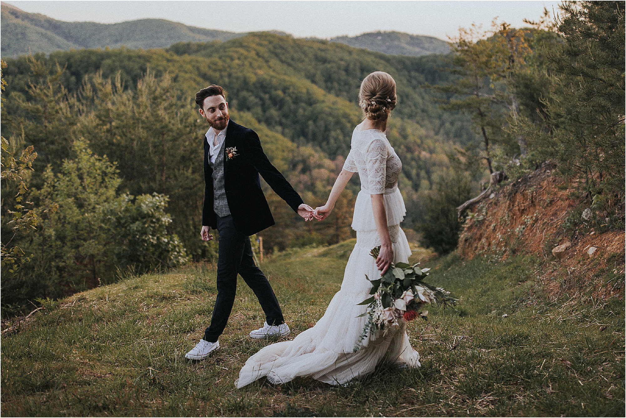 bride and groom walk past each other overlooking mountains