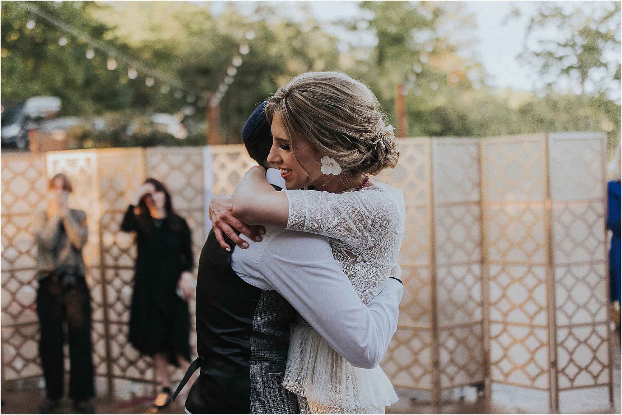 bride and groom hug at wedding reception