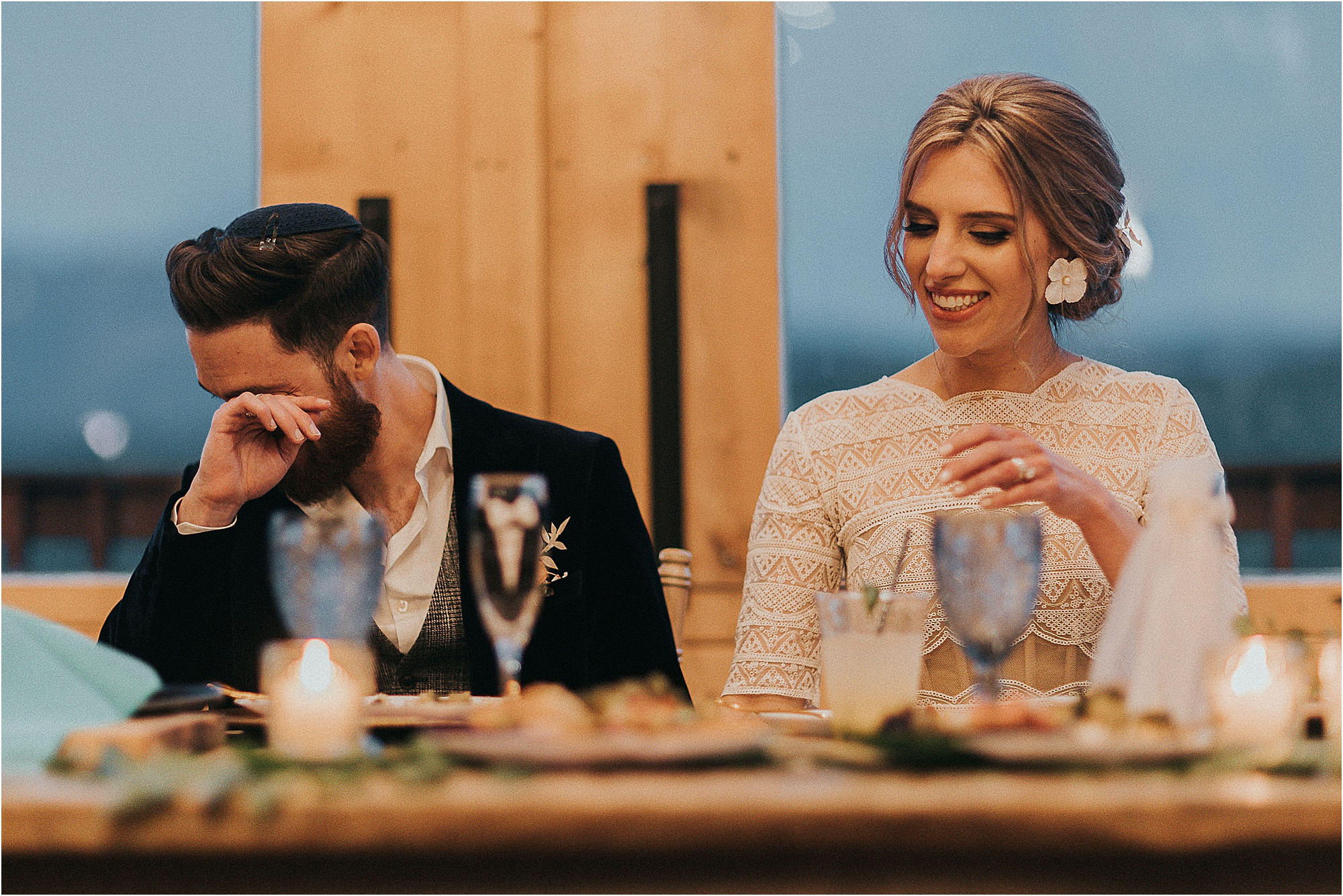 bride and groom sit at head table listening to toasts